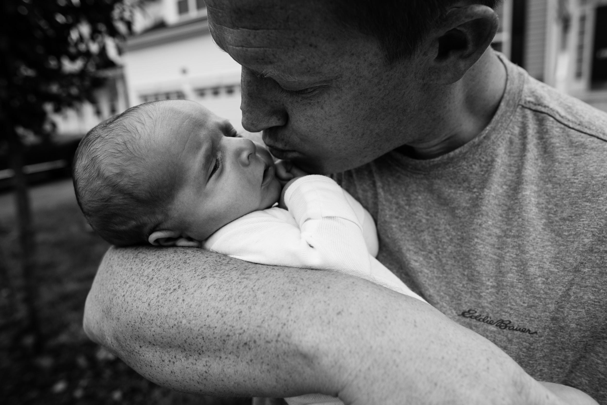 Dad kissing newborn son by Northern Virginia Family Photographer Nicole Sanchez