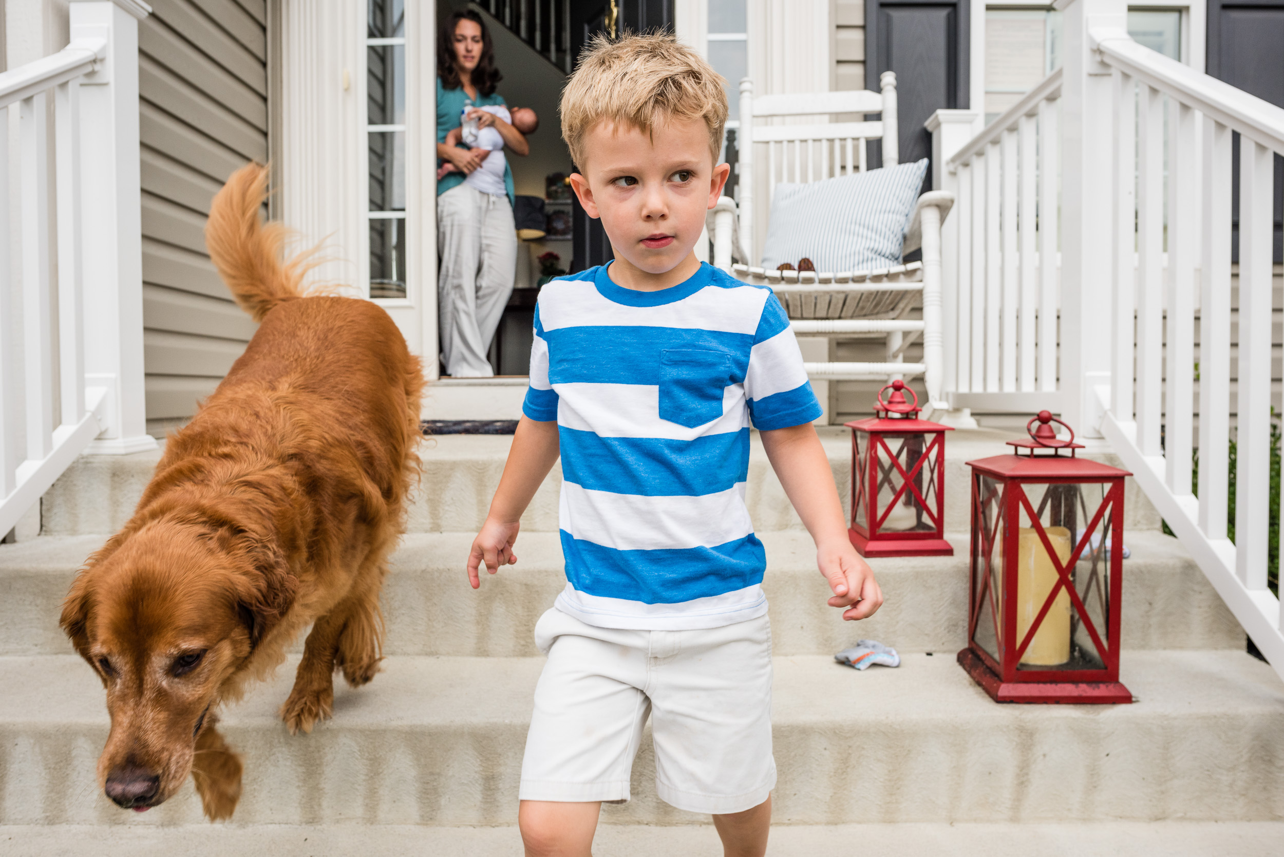Young boy heading out for walk with pet dog and mom with baby in Northern Virginia by Family Photographer Nicole Sanchez