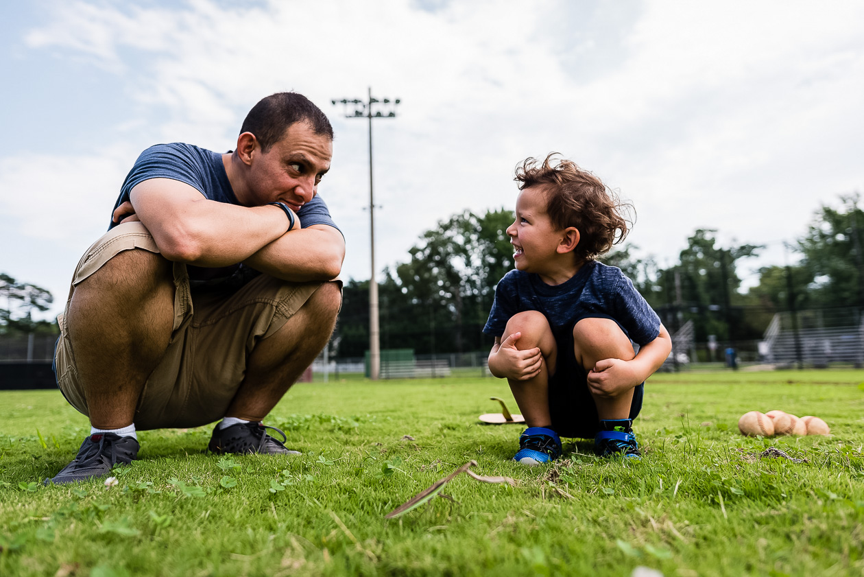 young boy looking at dad in field by northern virginia family photographer nicole sanchez