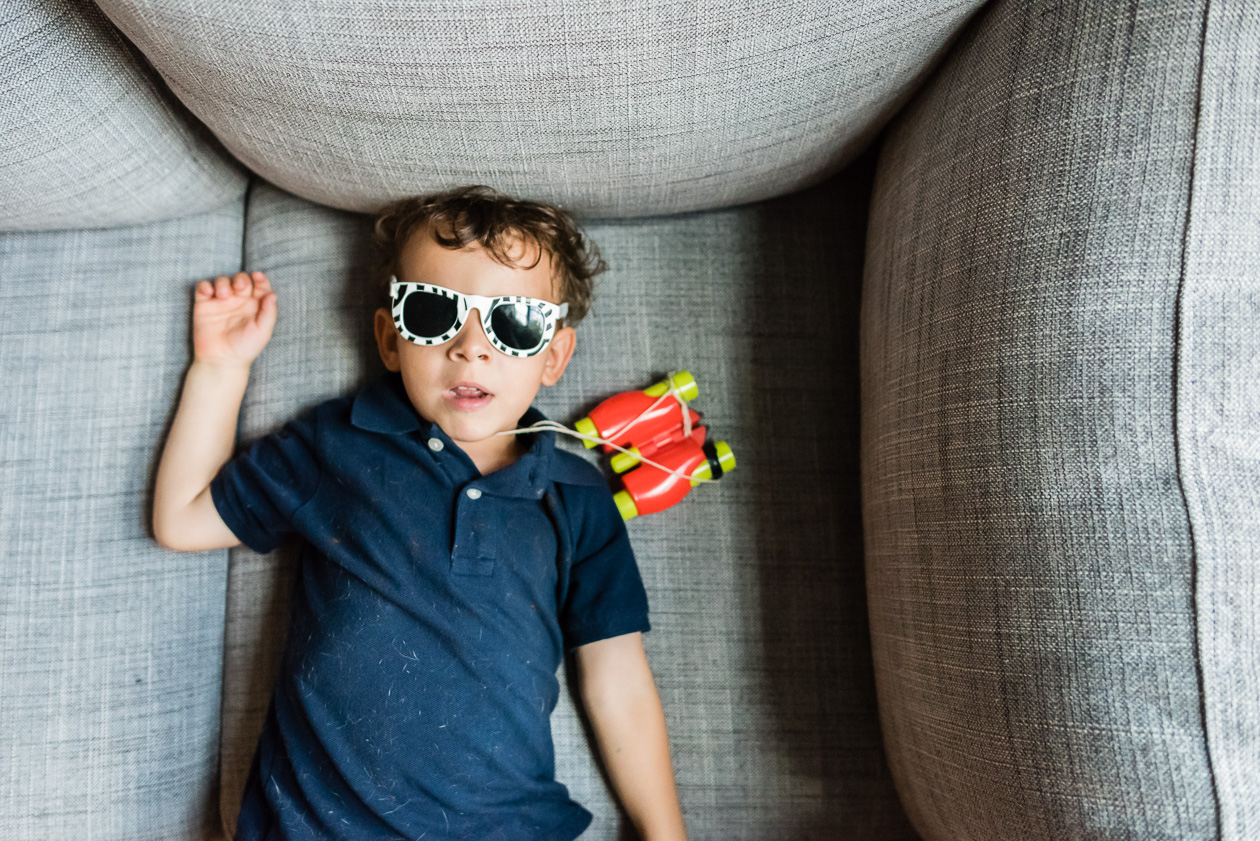 boy wearing sunglasses indoors by northern virginia family photographer nicole sanchez