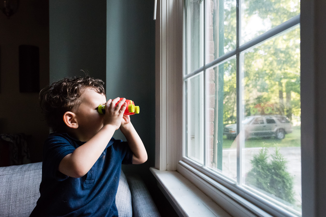 boy looking through toy binoculars by northern virginia family photographer nicole sanchez