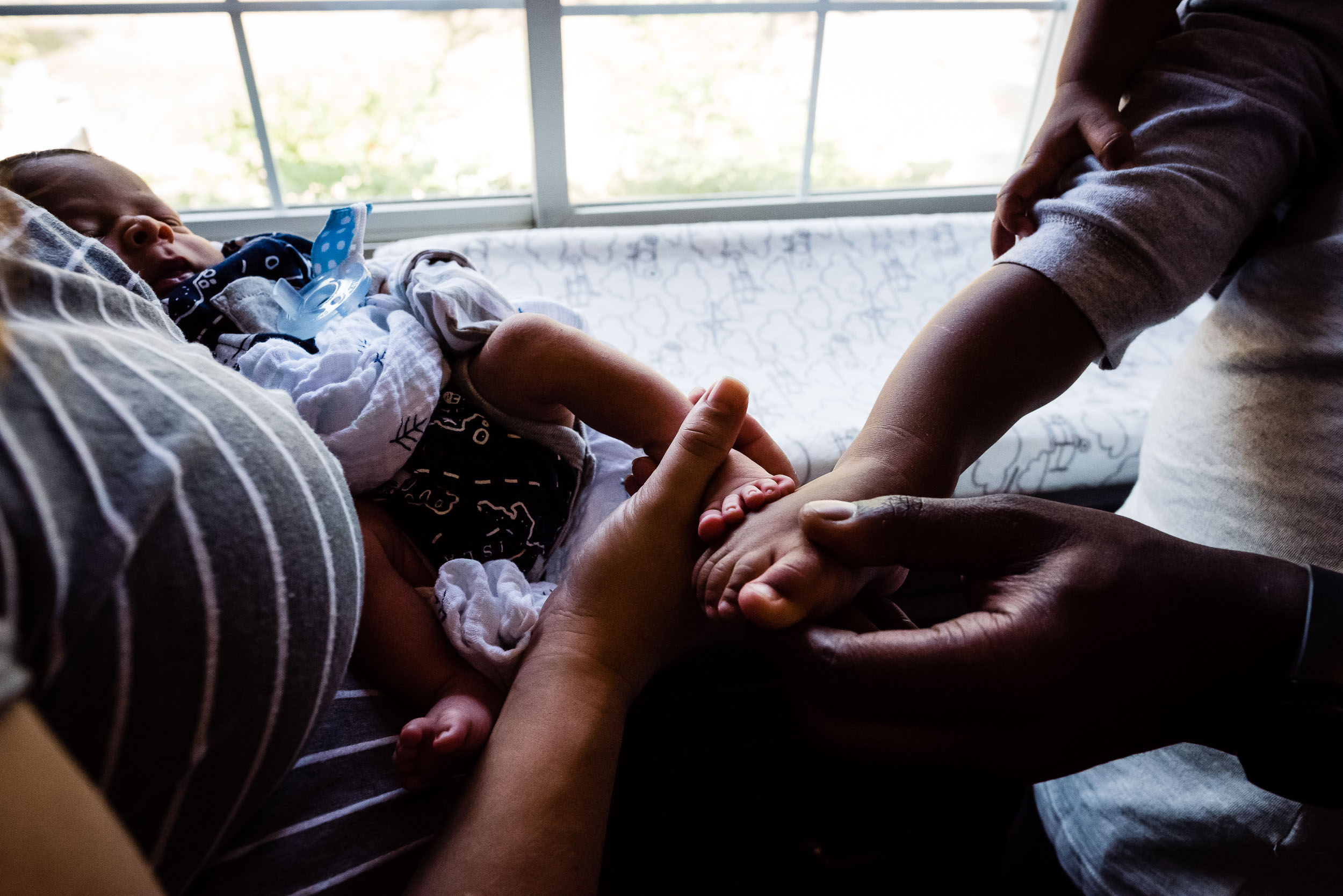 parents comparing toddler and newborn feet by family photographer nicole sanchez
