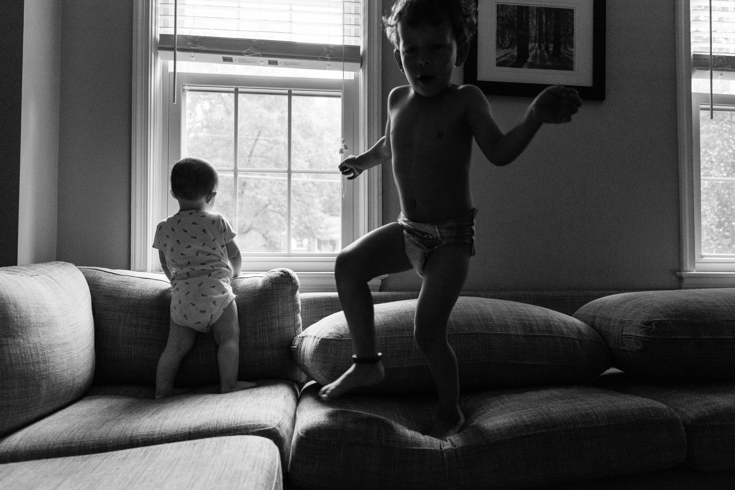 baby looking out window while brother jumps on couch by northern virginia family photographer nicole sanchez