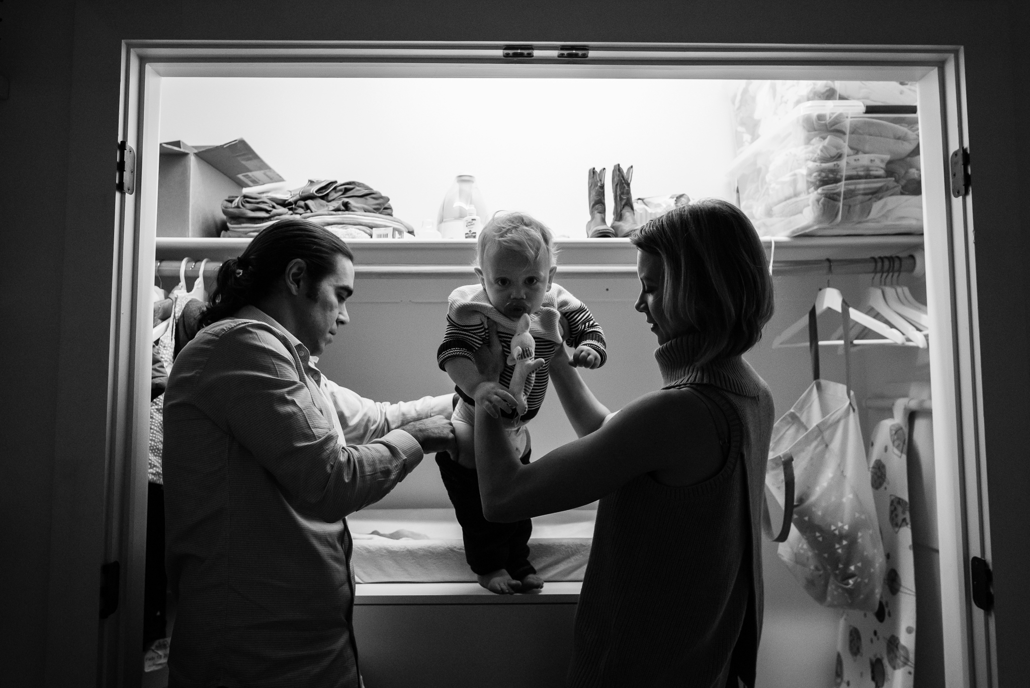 Parents putting pants on toddler boy in Washington, DC by Family Photographer Nicole Sanchez
