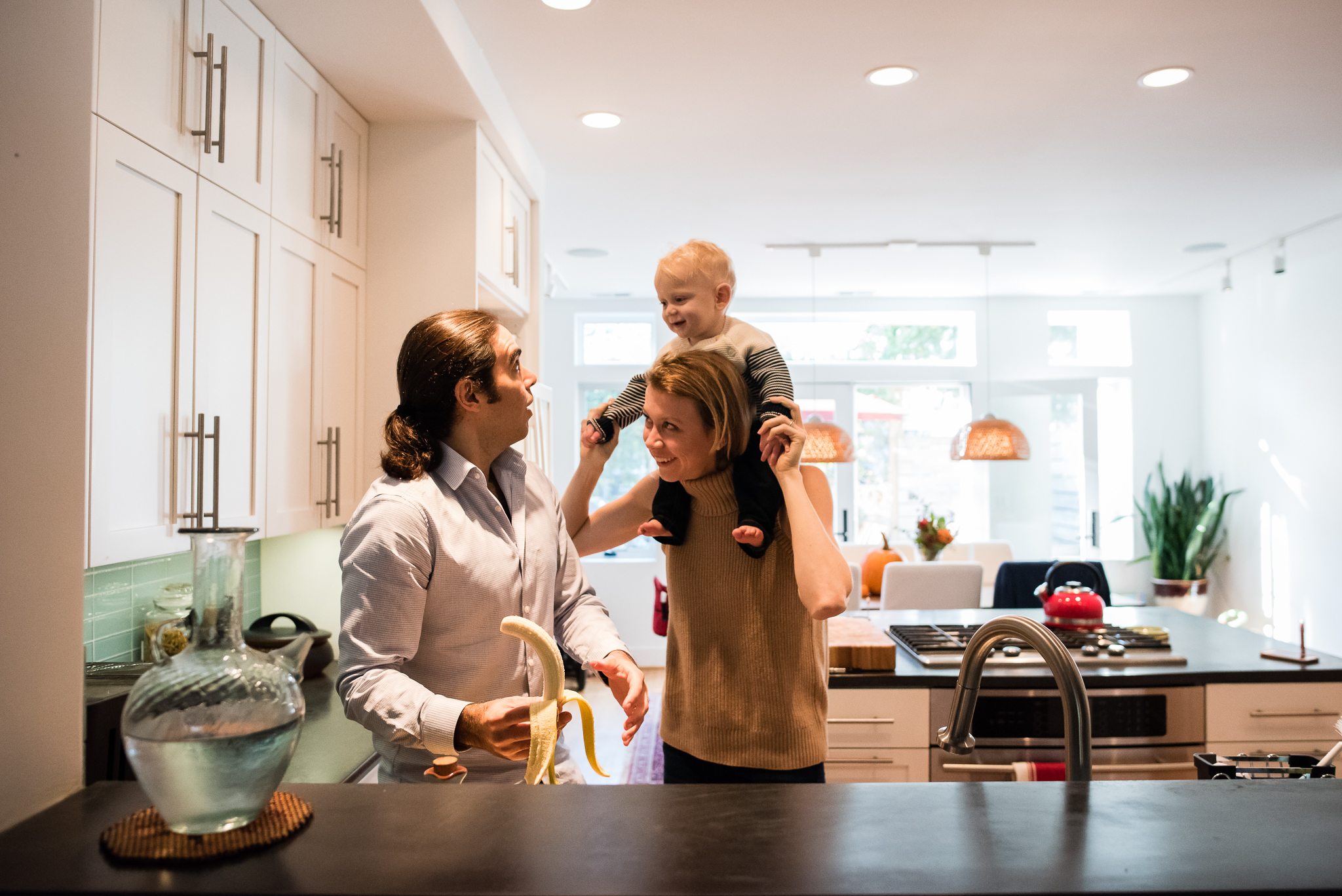 Mom and Dad playing with Baby in Washington, DC kitchen by Family Photographer Nicole Sanchez