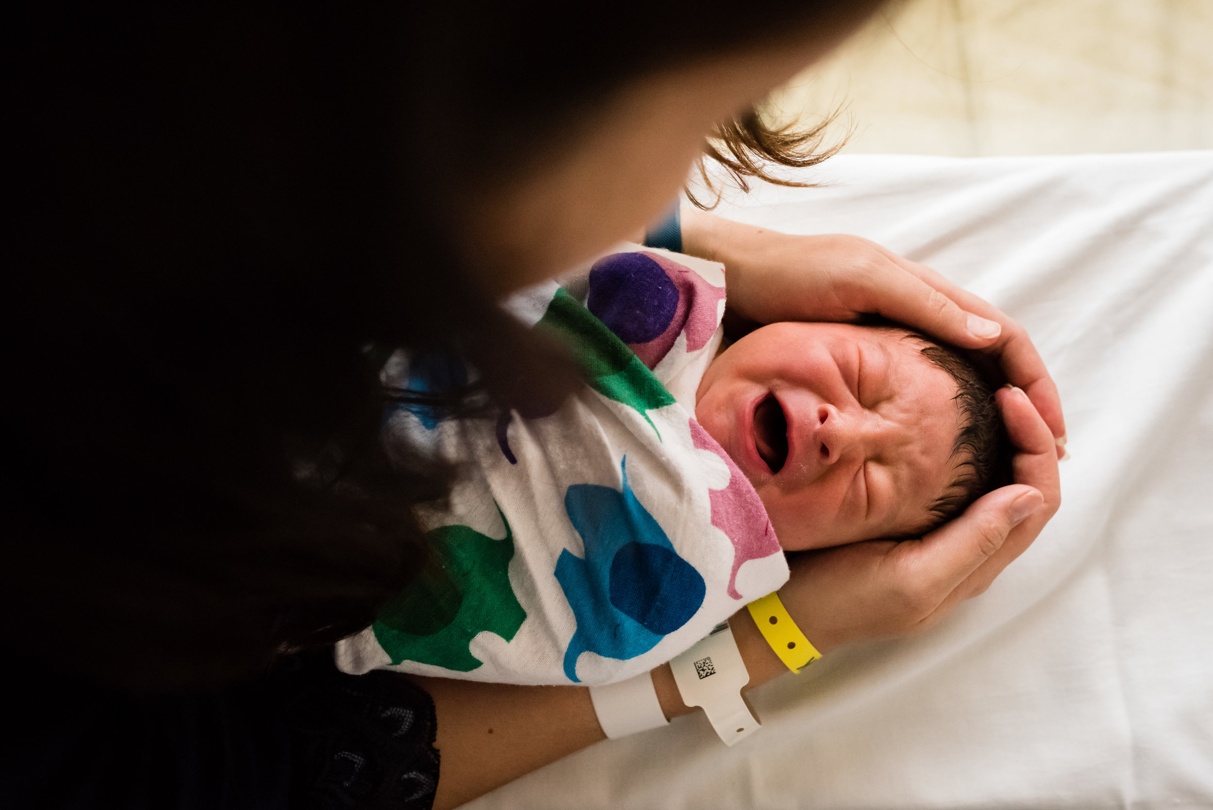 Mom comforting newborn baby in hospital crib by Northern Virginia Family Photographer Nicole Sanchez