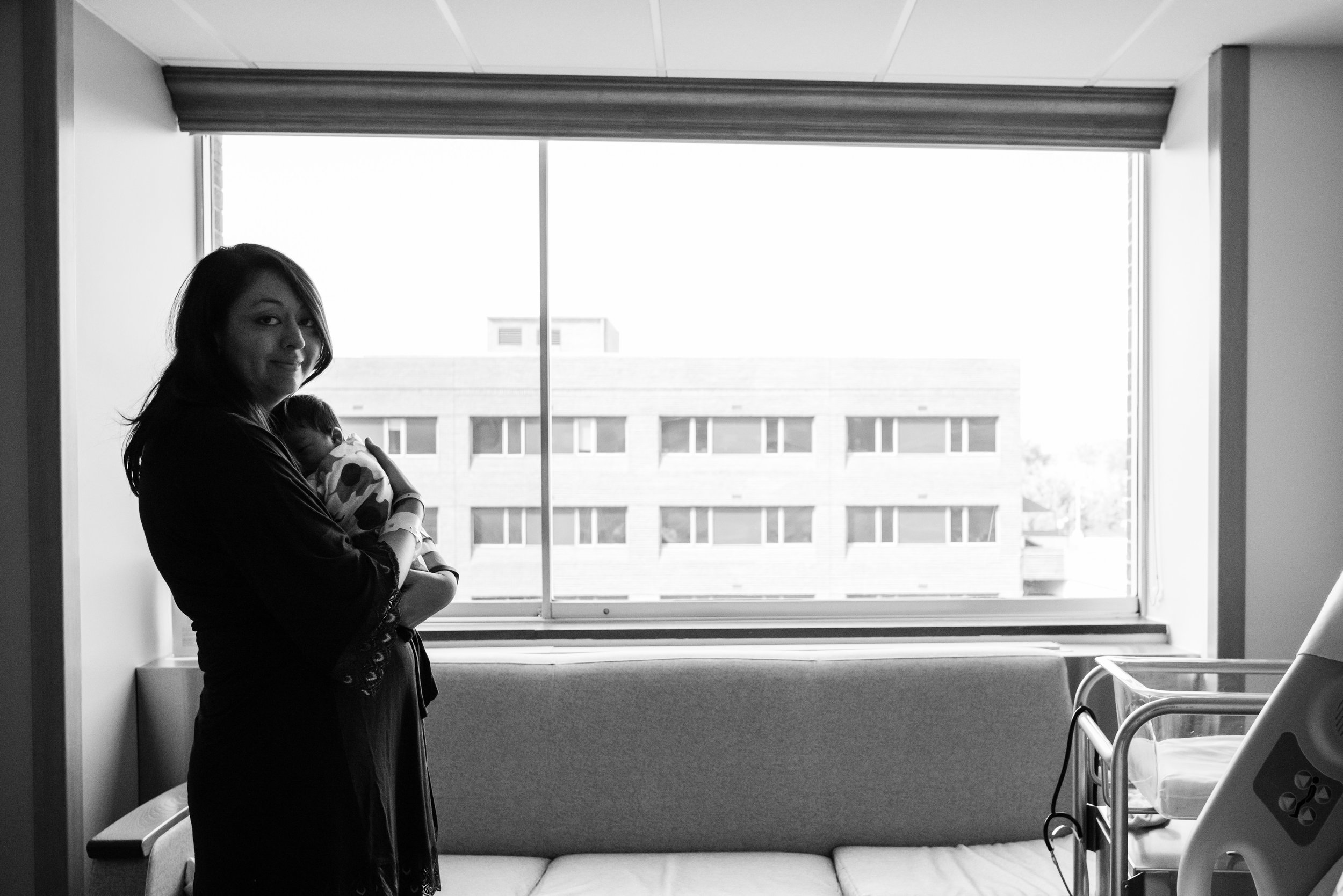 New mom holding baby in front of hospital window by Northern Virginia Newborn Photographer Nicole Sanchez