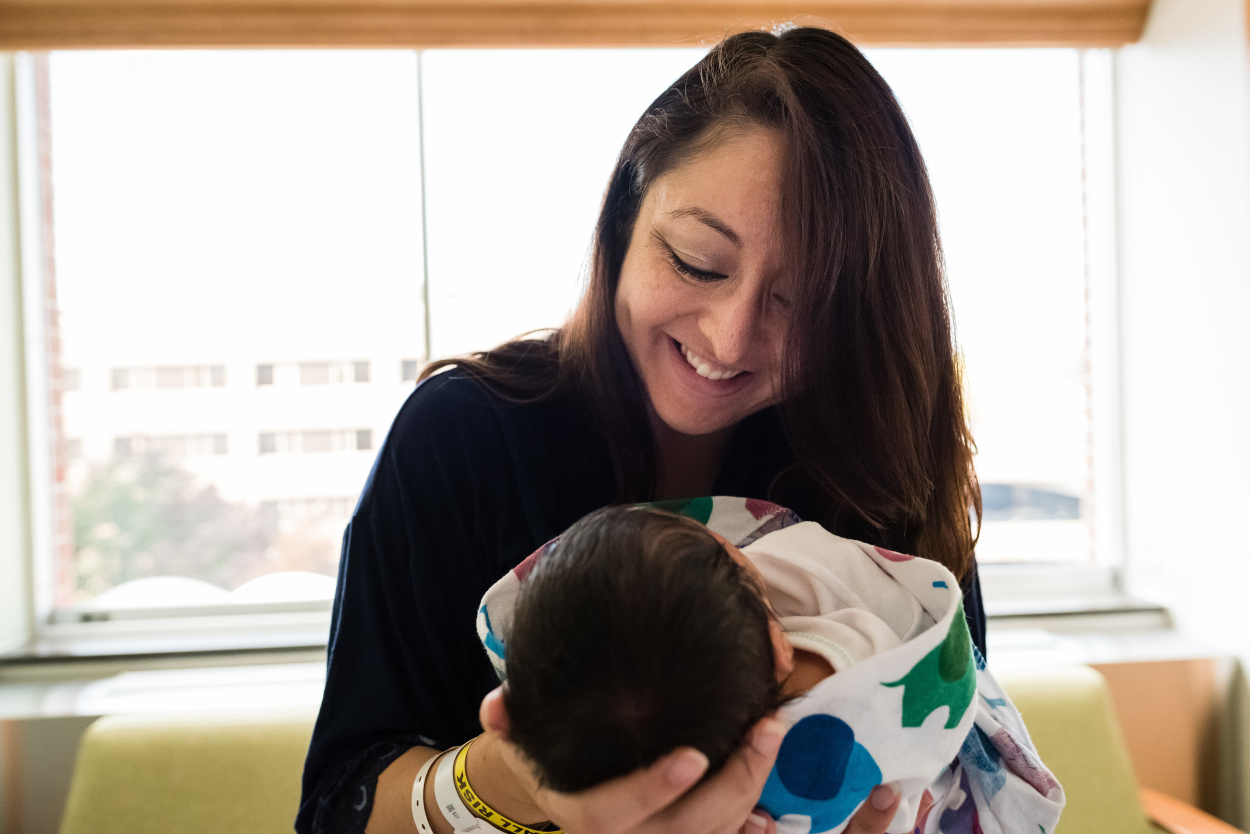 Happy mom smiling at newborn in Northern Virginia Hospital by Family photographer Nicole Sanchez