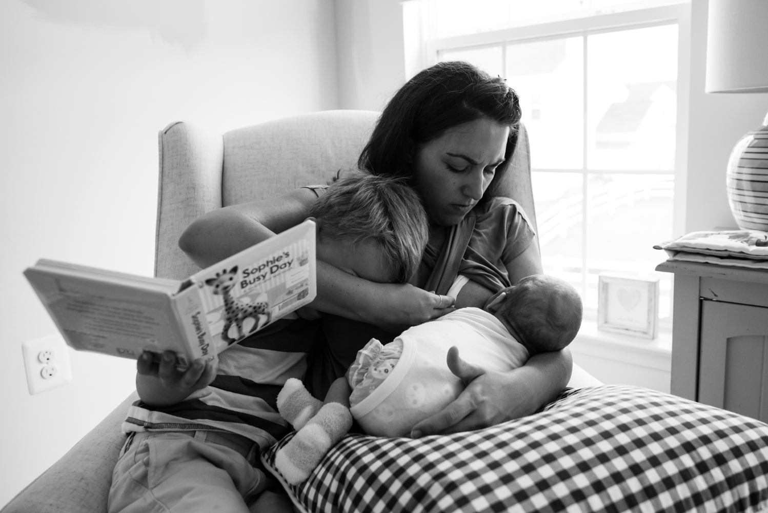 Mom trying to nurse newborn while reading to older son