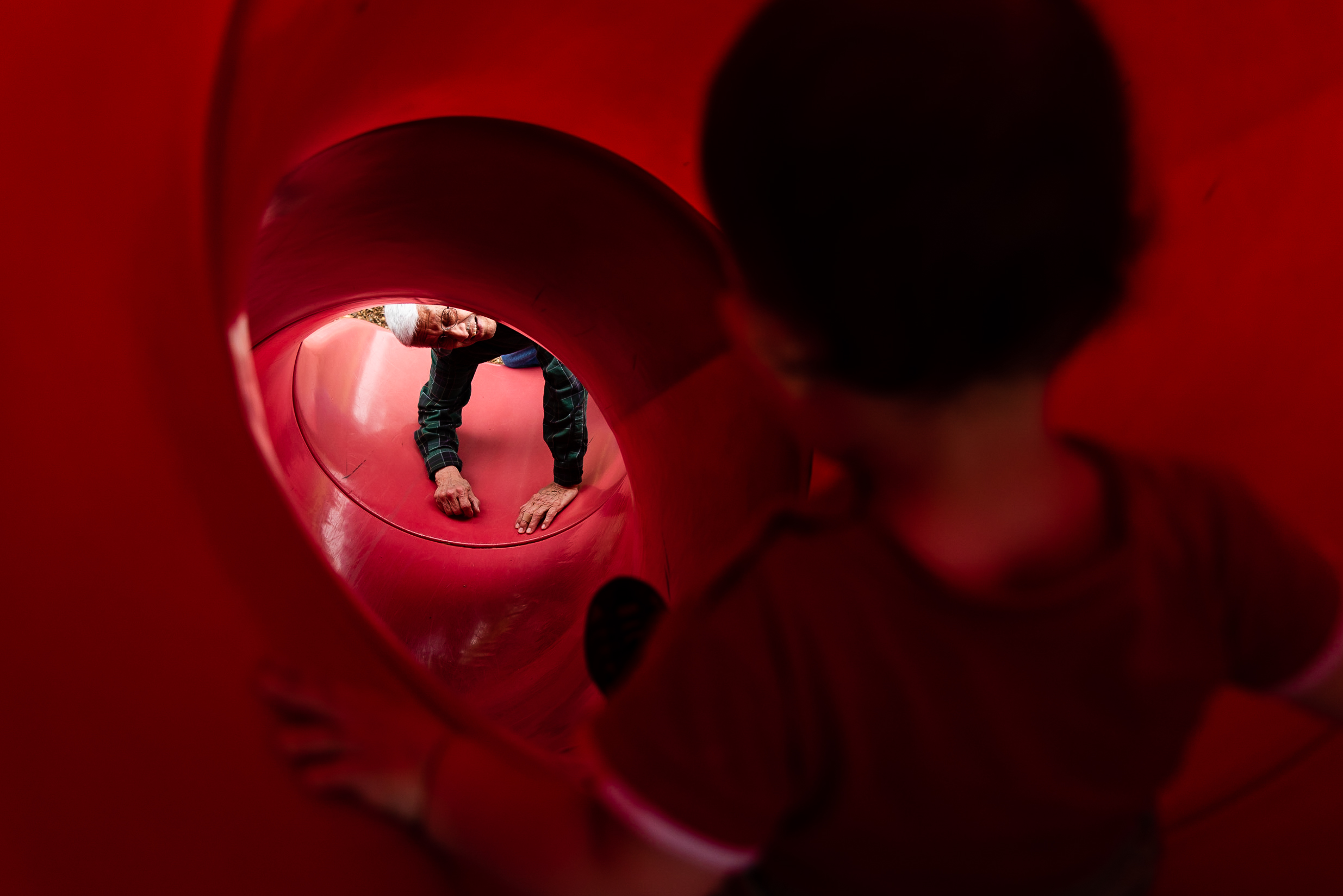 Grandfather waiting at bottom of tunnel slide by Northern Virginia Family Photographer Nicole Sanchez
