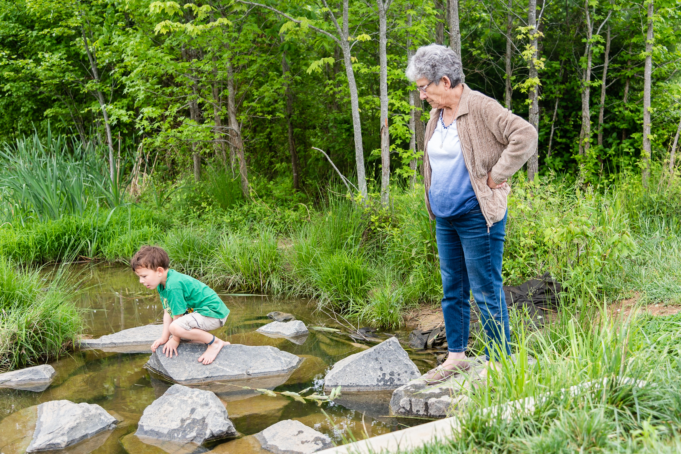 Grandmother and grandson exploring creek by Northern Virginia Family Photographer Nicole Sanchez