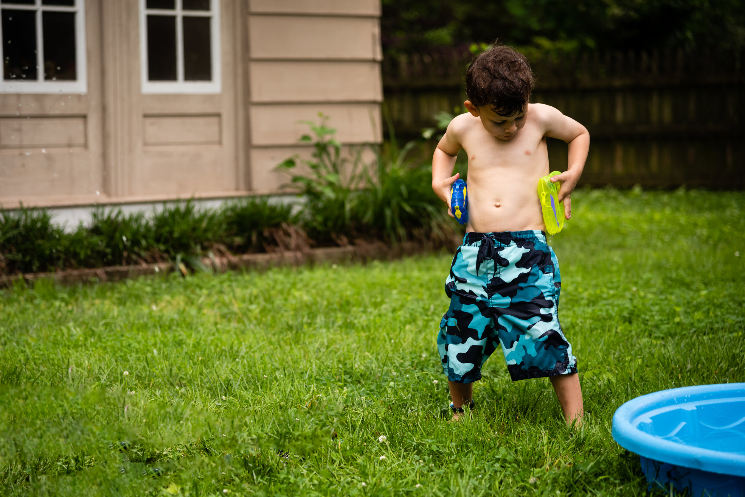 Boy pretending to holster water guns by Northern Virginia Family Photographer Nicole Sanchez