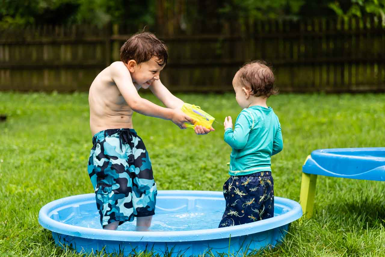 Big brother shooting toddler with water gun by Northern Virginia Family Photographer Nicole Sanchez