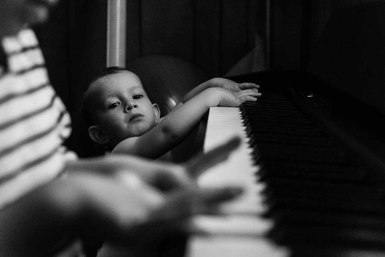 Toddler watching big brother play piano by Northern Virginia Family Photographer Nicole Sanchez