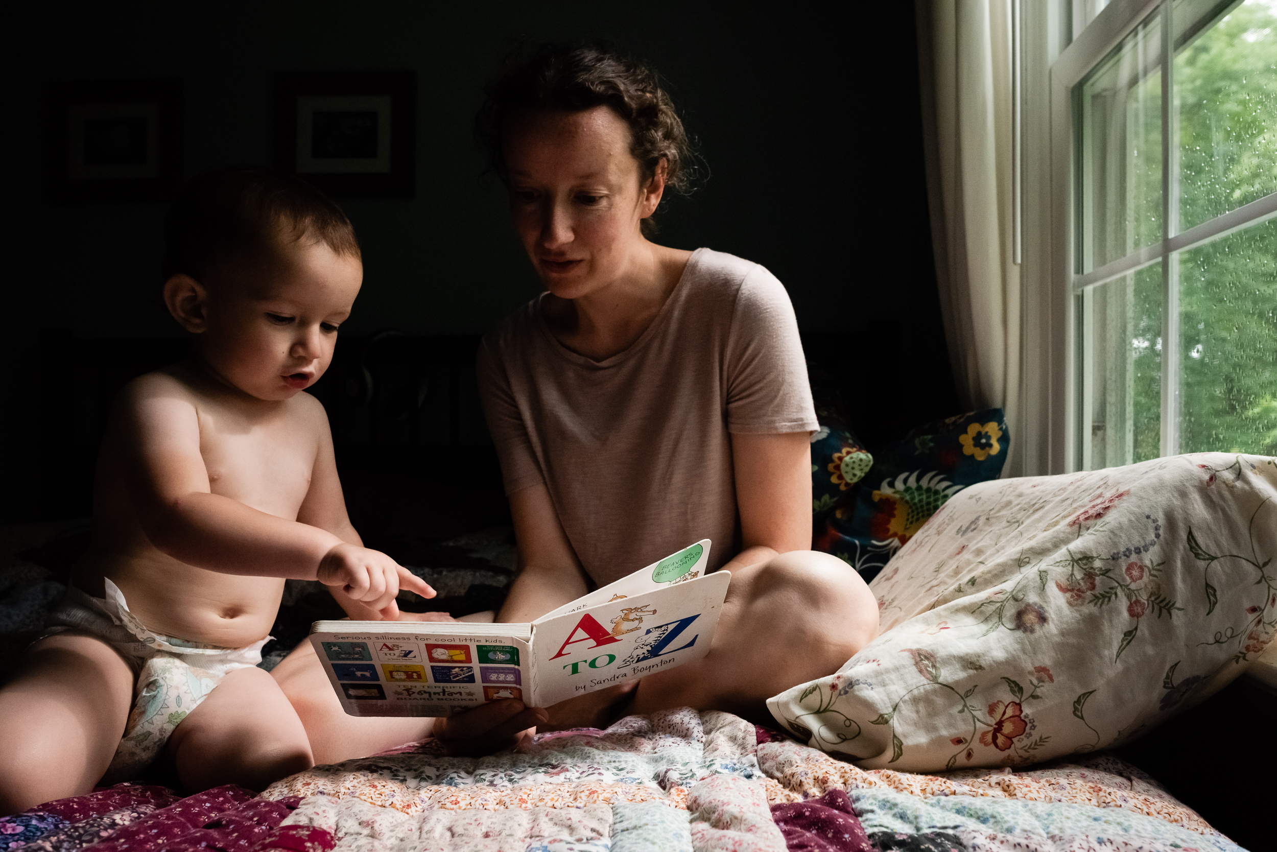Mother reading to toddler son in bed by Northern Virginia Family Photographer Nicole Sanchez