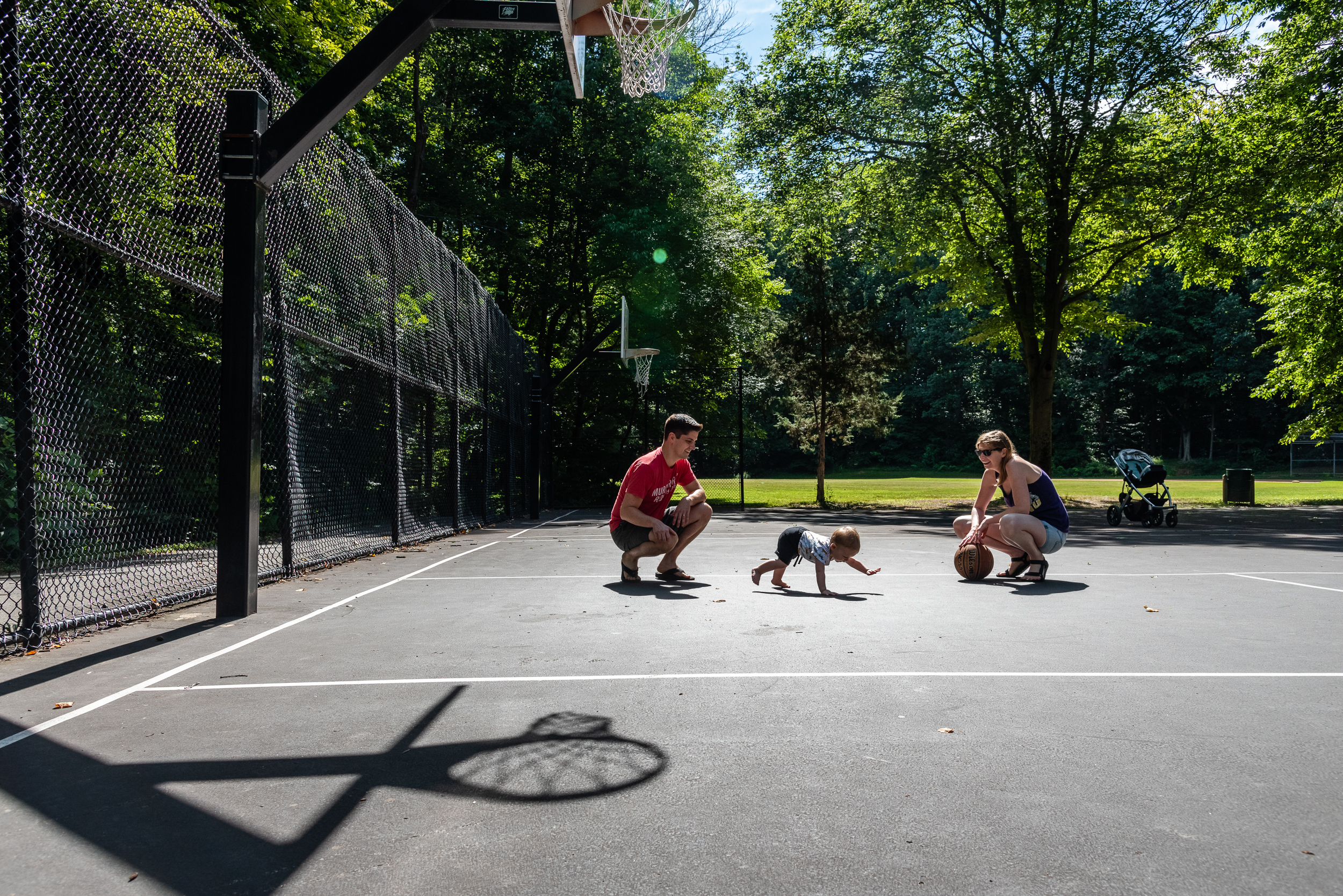 mom and dad playing basketball with toddler at northern virginia park by family photographer nicole sanchez