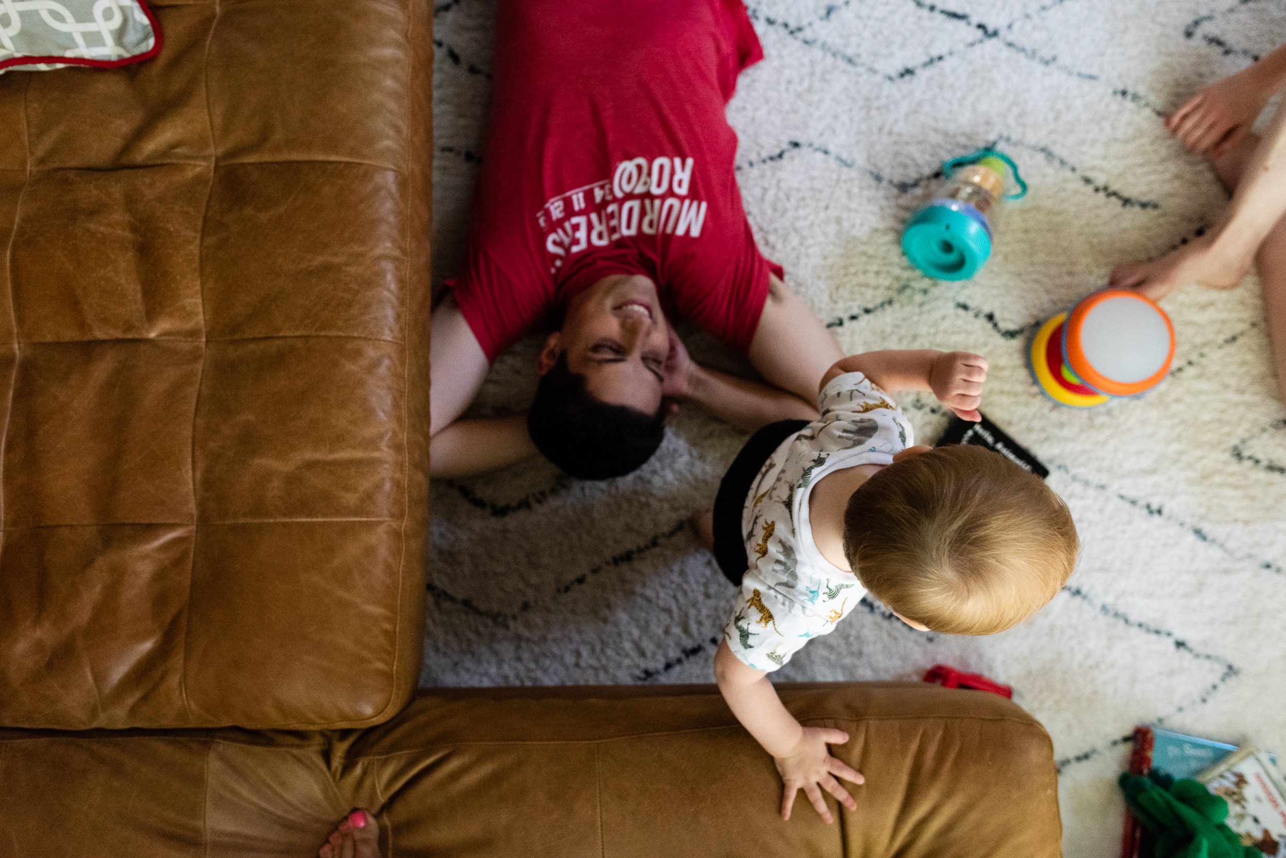 Dad laying on living room floor while toddler plays by northern virginia family photographer nicole sanchez