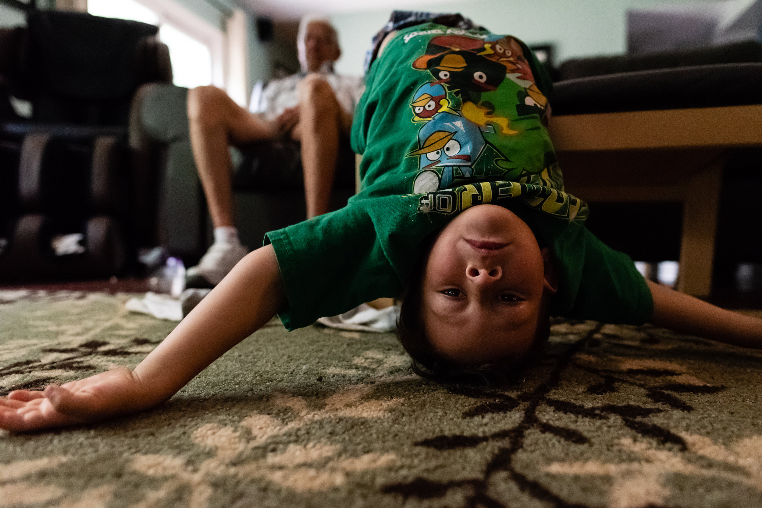 Boy hanging upside down off couch by Northern Virginia Family Photographer Nicole Sanchez
