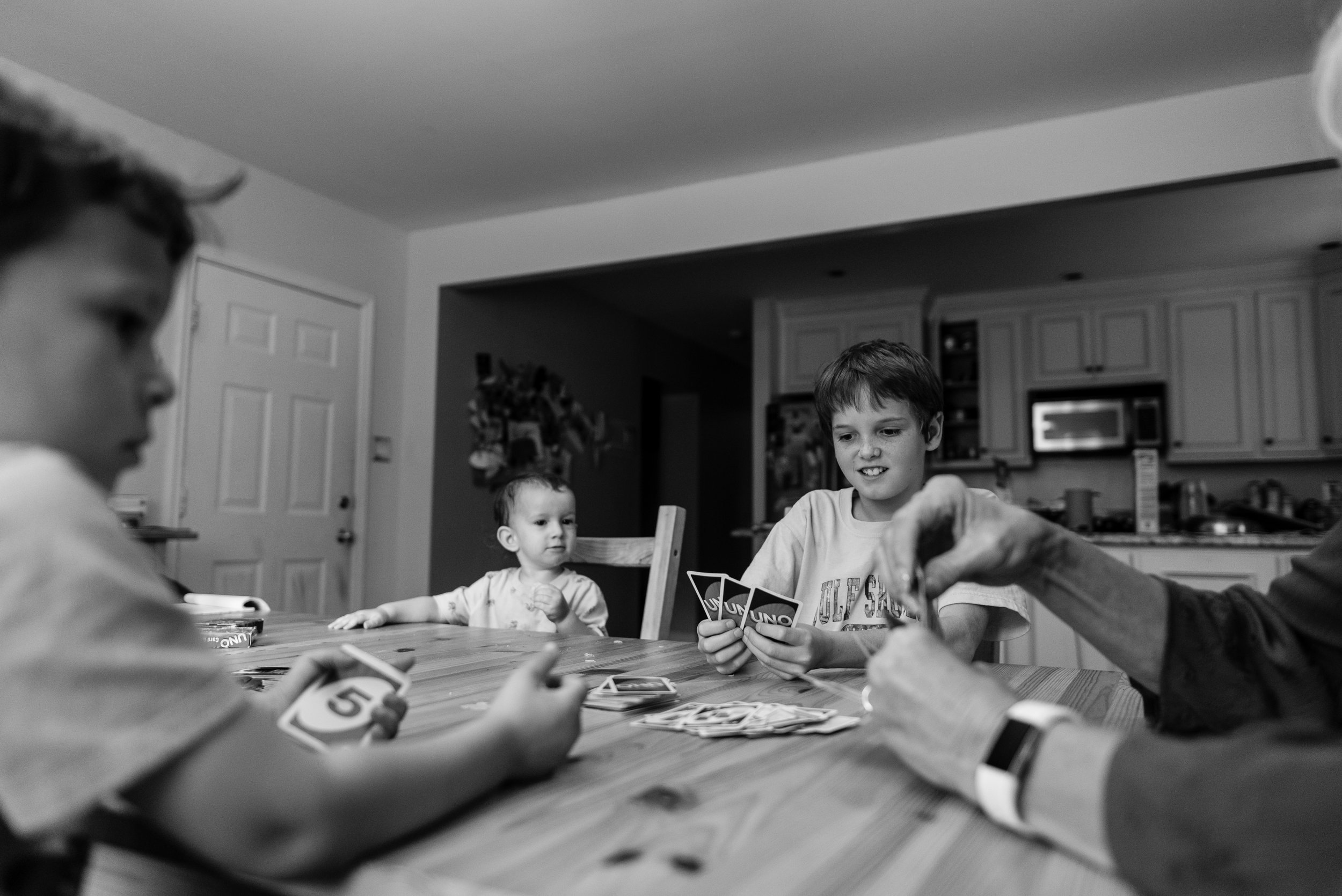 Family playing cards together at kitchen table by Northern Virginia Family Photographer Nicole Sanchez