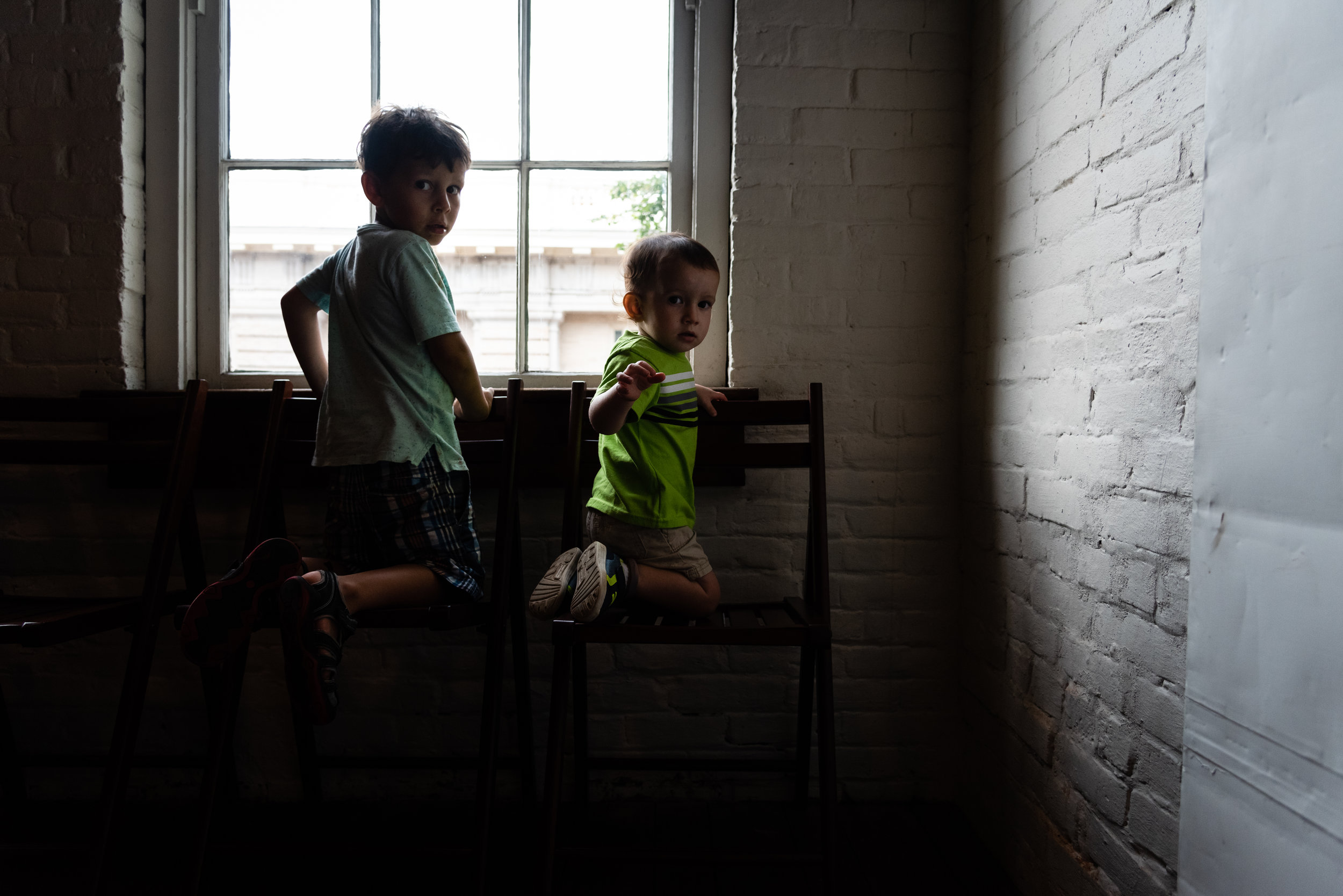 Boys looking out window at Stabler-Leadbeater Apothecary Museum by Northern Virginia Family Photographer Nicole Sanchez