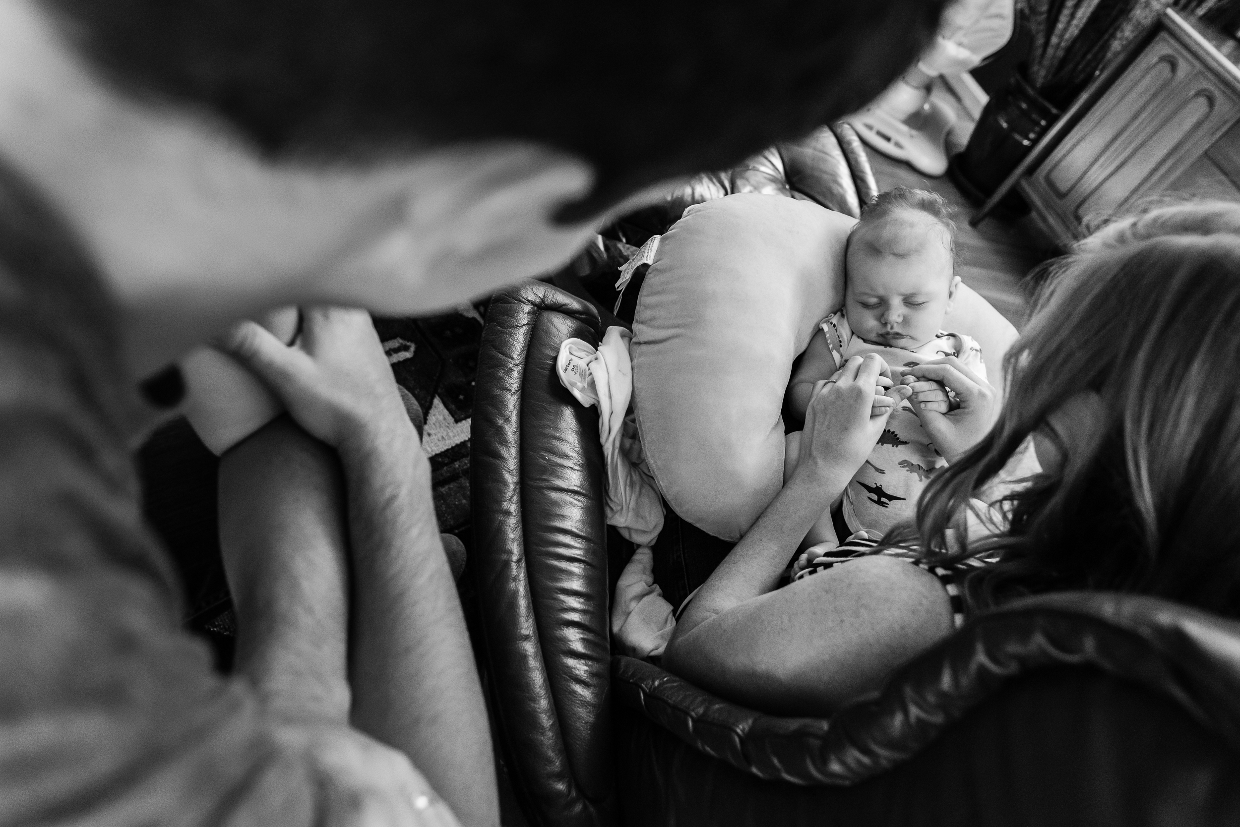 Looking over Dad's shoulder looking at new baby by Northern Virginia Family Photographer Nicole Sanchez