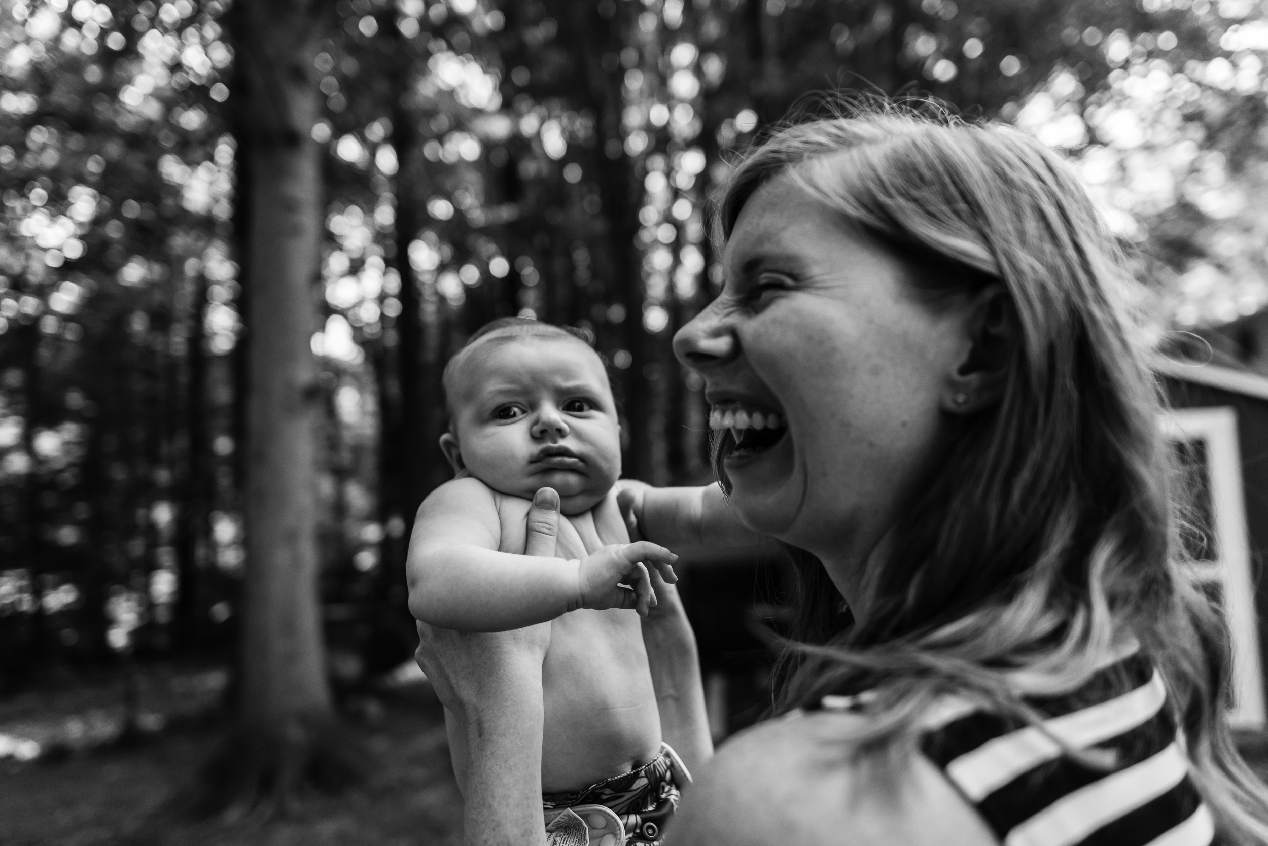 Mom laughing with new baby outside by Northern Virginia Newborn Photographer Nicole Sanchez