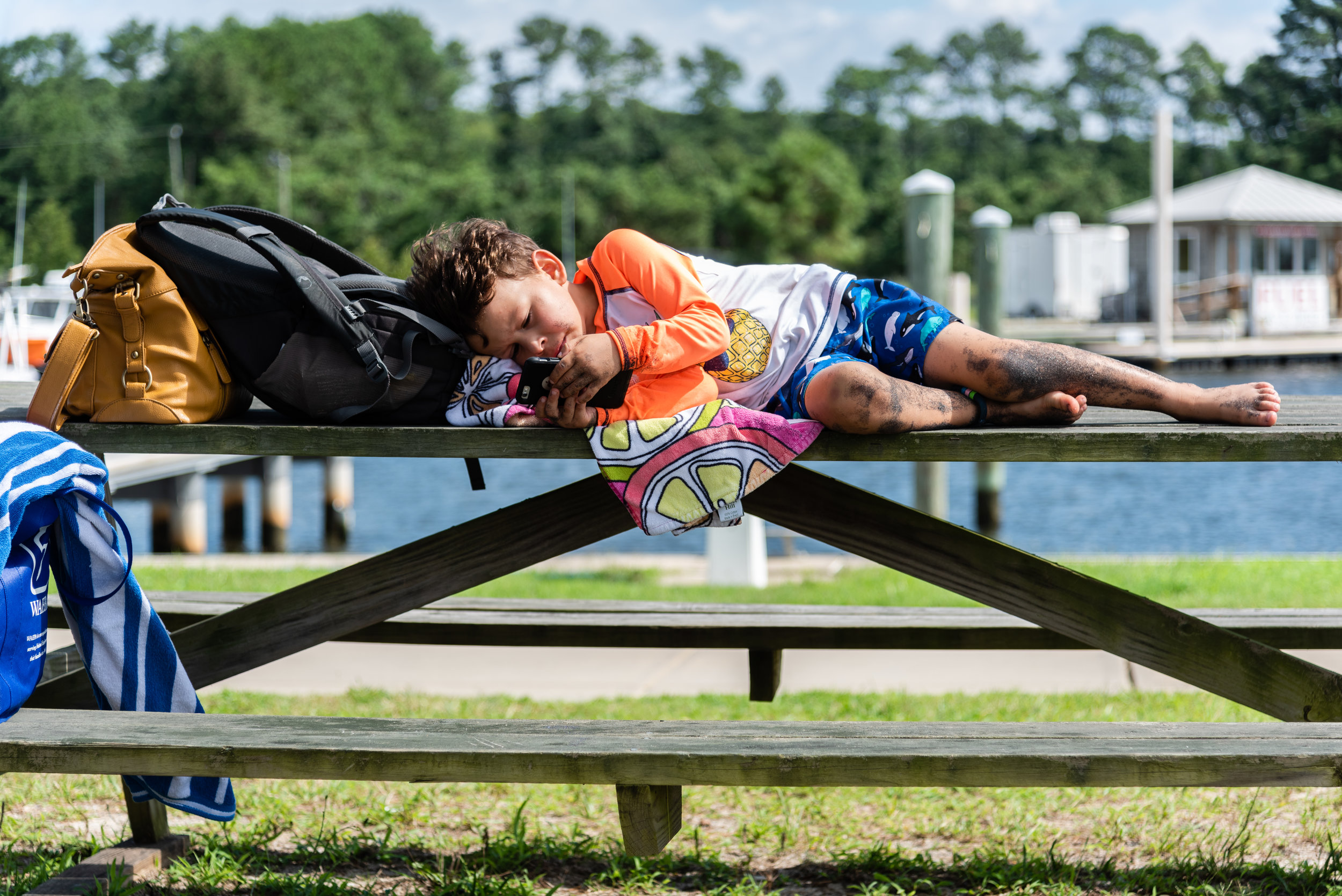 Boy laying on picnic table with iphone by Northern Virginia Family Photographer Nicole Sanchez
