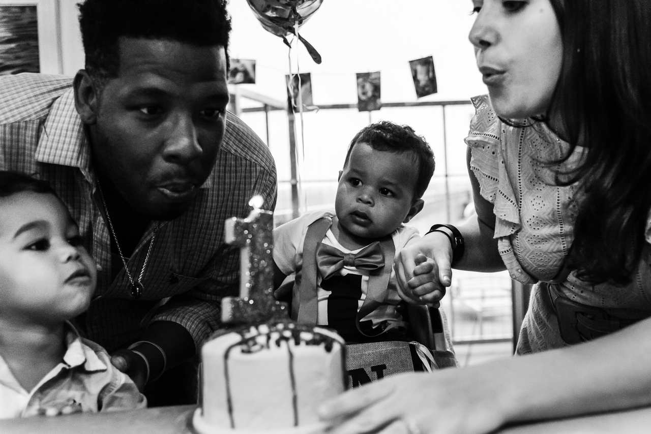 Mom dad and big brother helping baby blow out birthday candles by Northern Virginia Family Photographer Nicole Sanchez