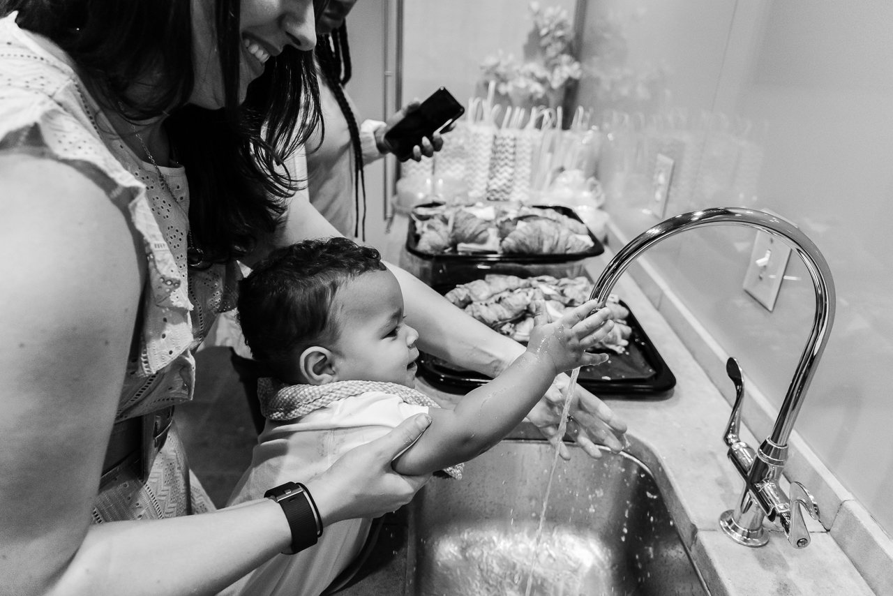 Mom washing cake off baby's hands
