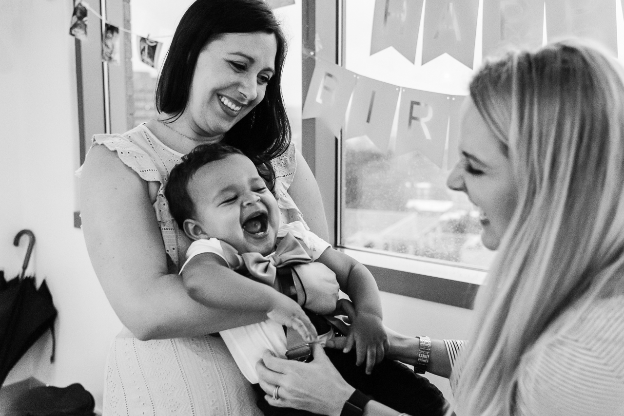 Mom holding laughing toddler at birthday party by Northern Virginia Family Photographer Nicole Sanchez
