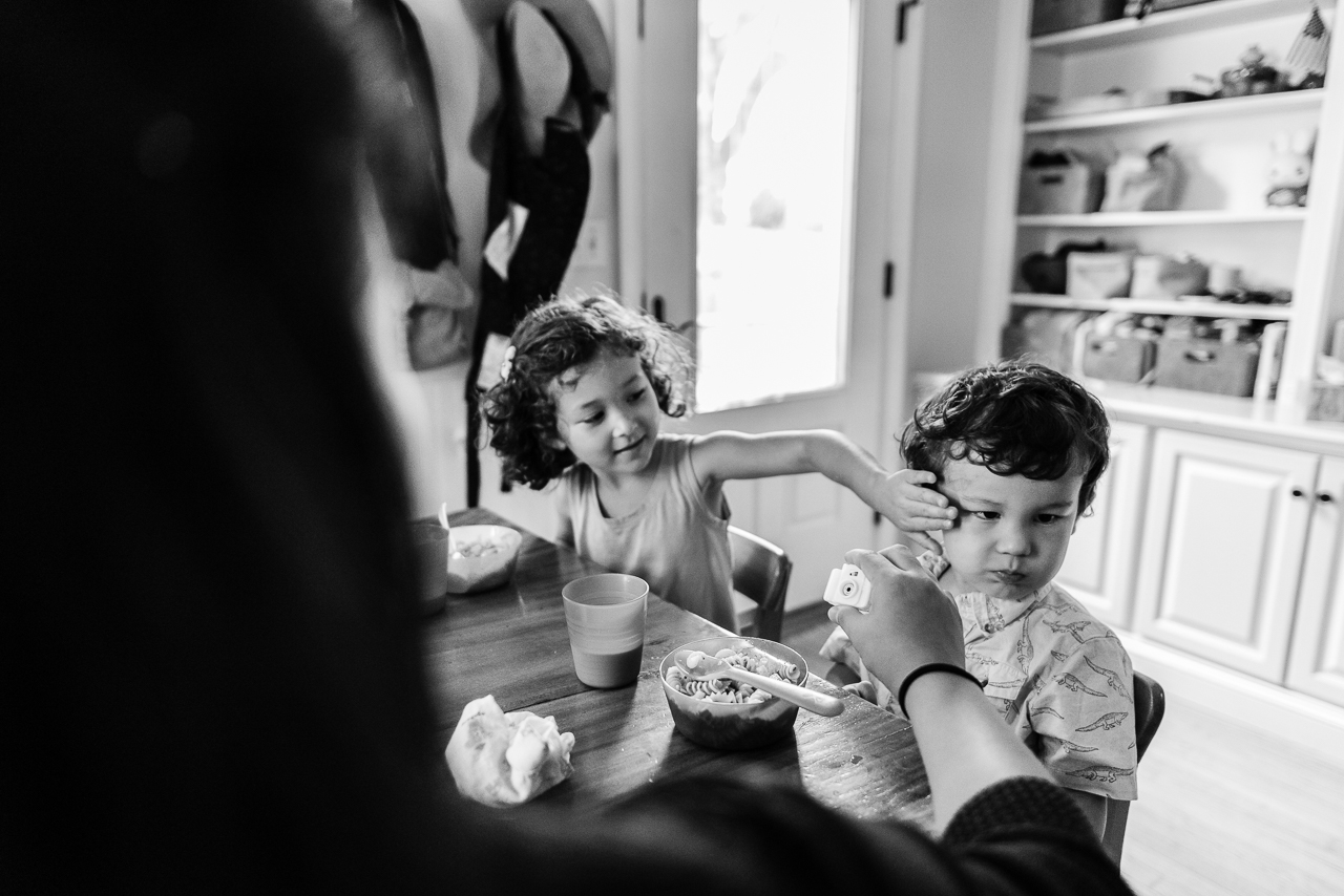 Young girl wiping little brother's face at kitchen table by Northern Virginia Family Photographer Nicole Sanchez