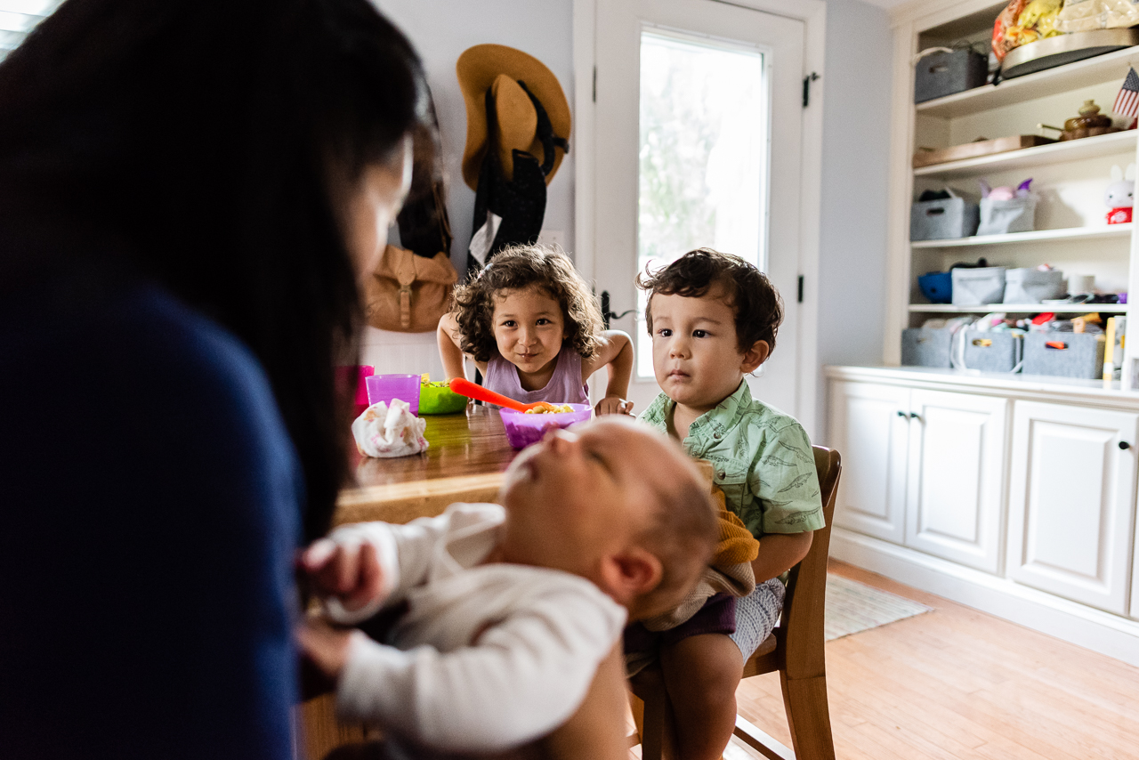 Mom with newborn and siblings having a snack at kitchen table by Northern Virginia Family Photographer Nicole Sanchez