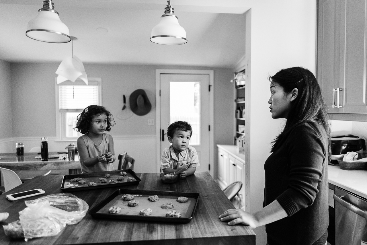 Mom at kitchen island giving baking instructions to son and daughter