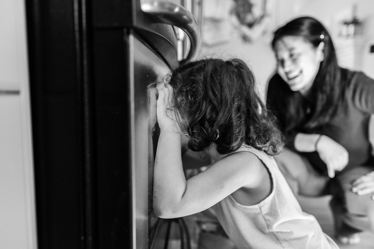 Mom smiling while watching kids wait for cookies to come out of oven by Northern Virginia Family Photographer Nicole Sanchez