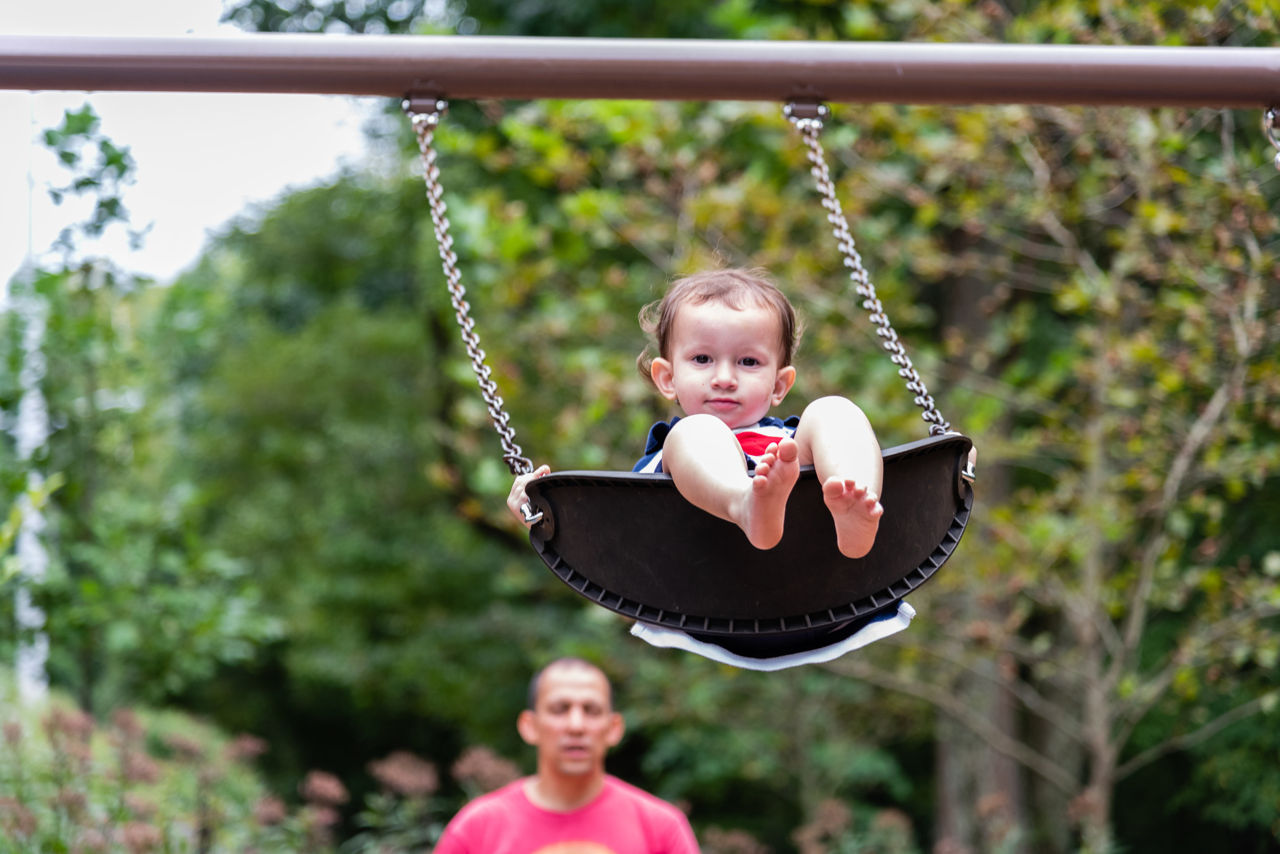 Toddler swinging on Northern Virginia playground with dad in background by Family Photographer Nicole Sanchez