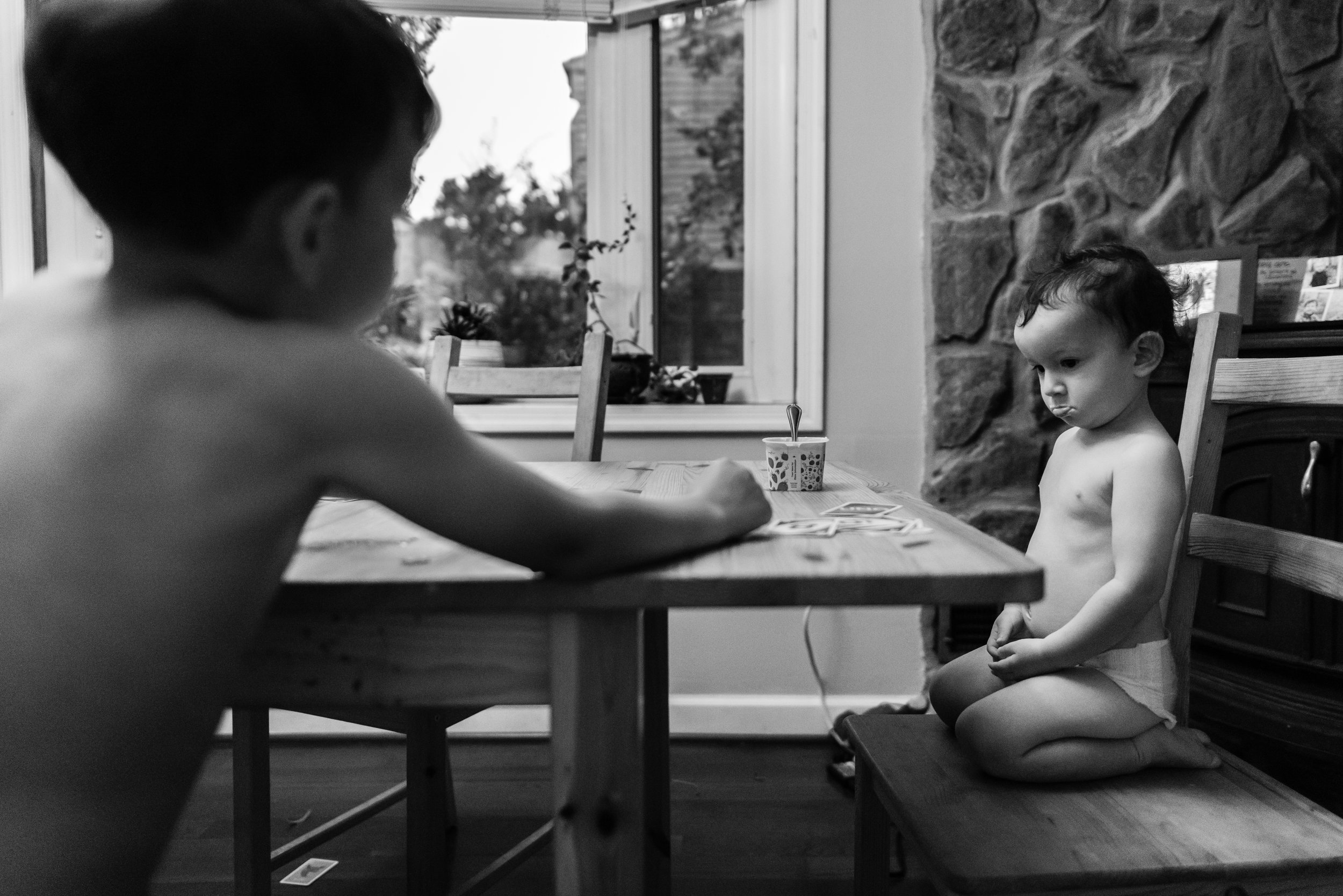 Little boy pouting at big brother while playing Uno by Family Photographer Nicole Sanchez