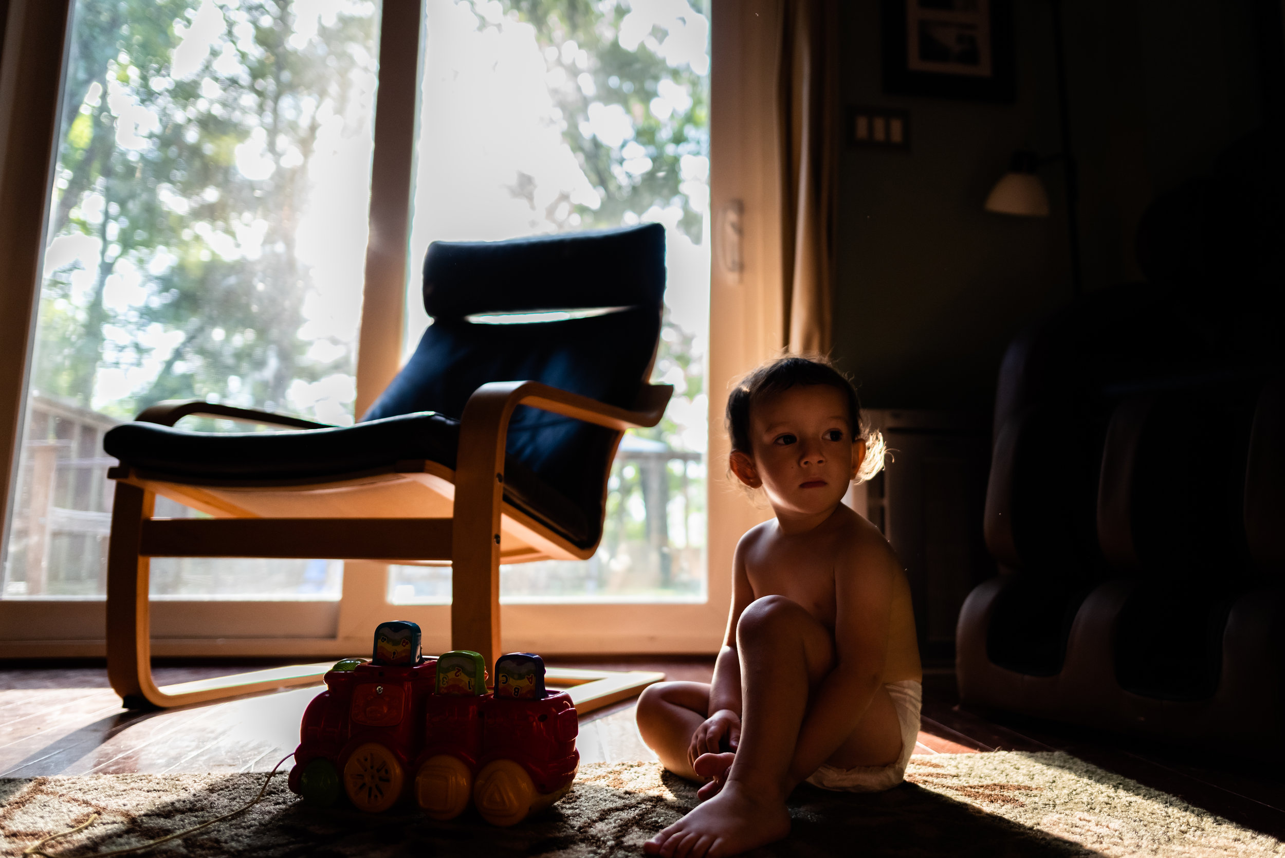 Little boy sitting on floor in pretty morning light by Family Photographer Nicole Sanchez