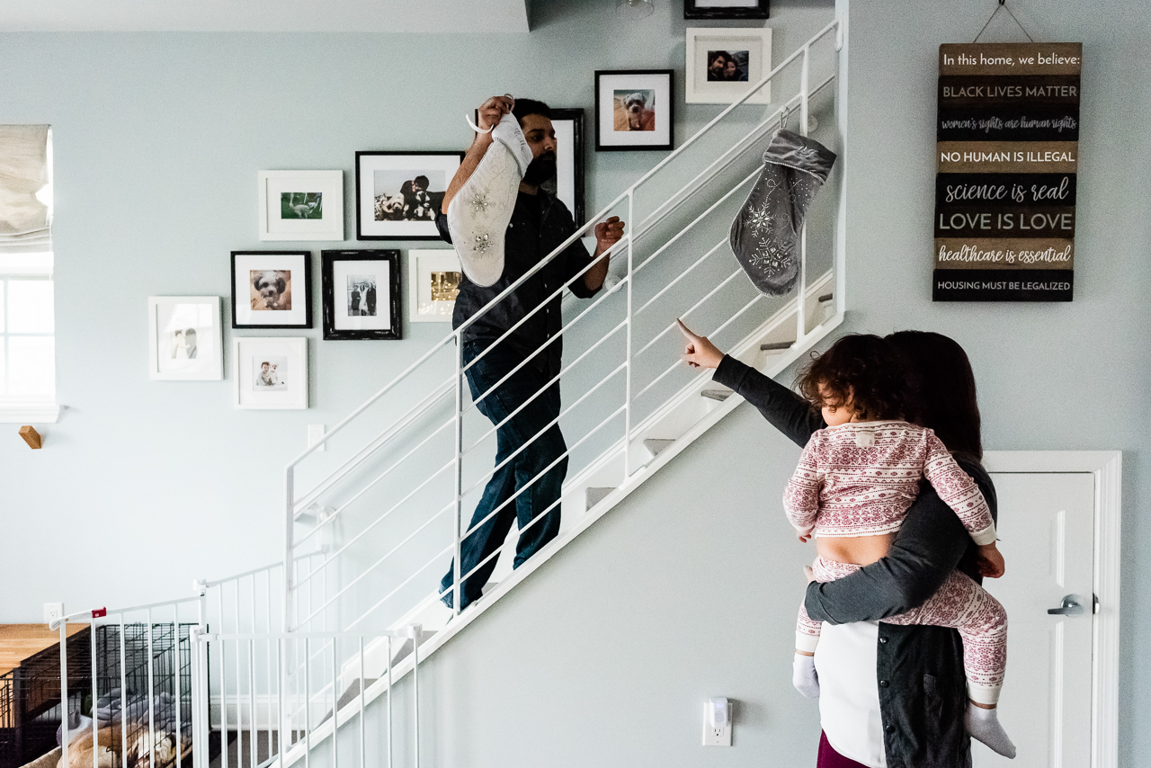 Dad hanging stocking on staircase with Mother and daughter