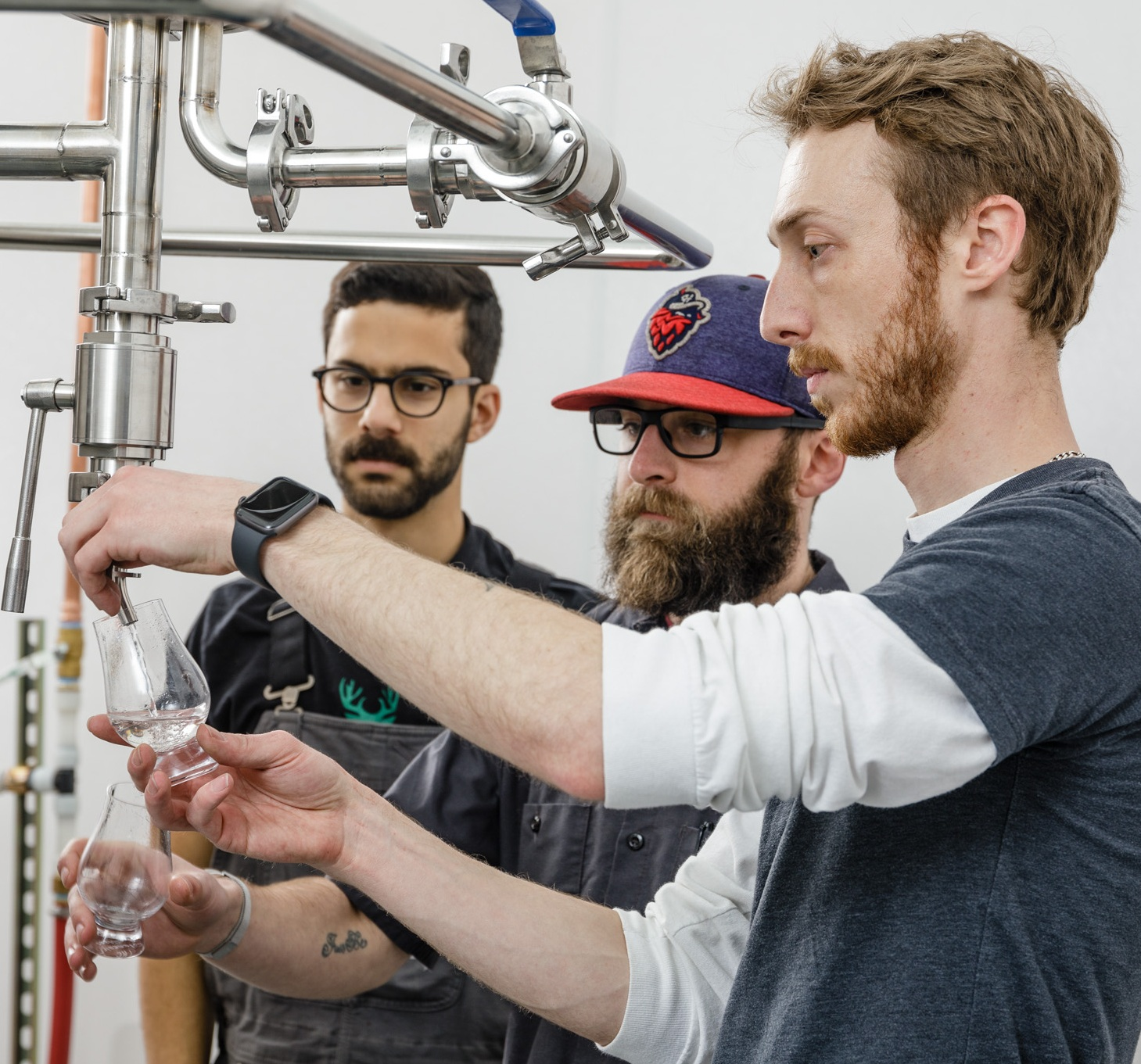 Distiller Travis Schoney samples gin distillate coming off the newly installed, custom 500 gallon still. Pictured are assistant distillers Kyle Ligoudice and Joshua Kaul.