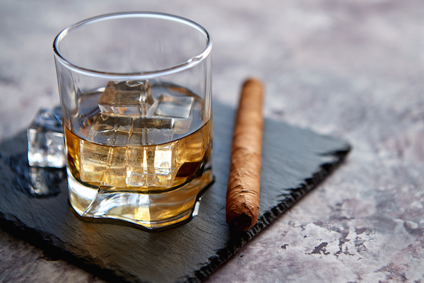 glass-of-whiskey-with-ice-cubes-and-cigar-MNQ2X5K.jpg