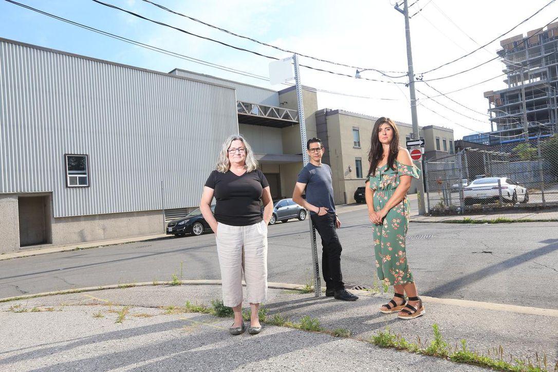 Three artists standing in front of Akin River art studio at 7 Labatt Ave in Toronto.