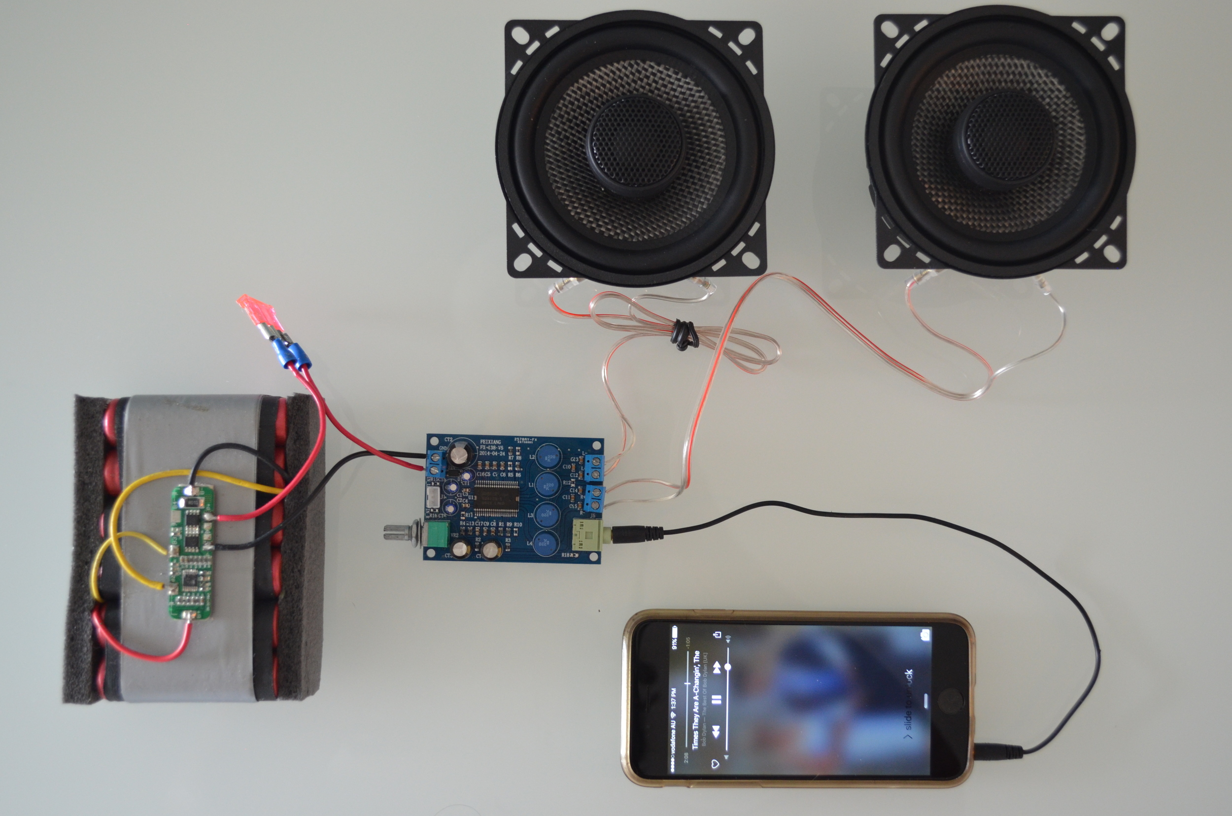 This photo shows the critical components of every audio system. The amplifier is receiving the audio signal from the iPhone. The amplifier 'boosts' the signal via the energy provided by the battery and sends the signal to the speakers.