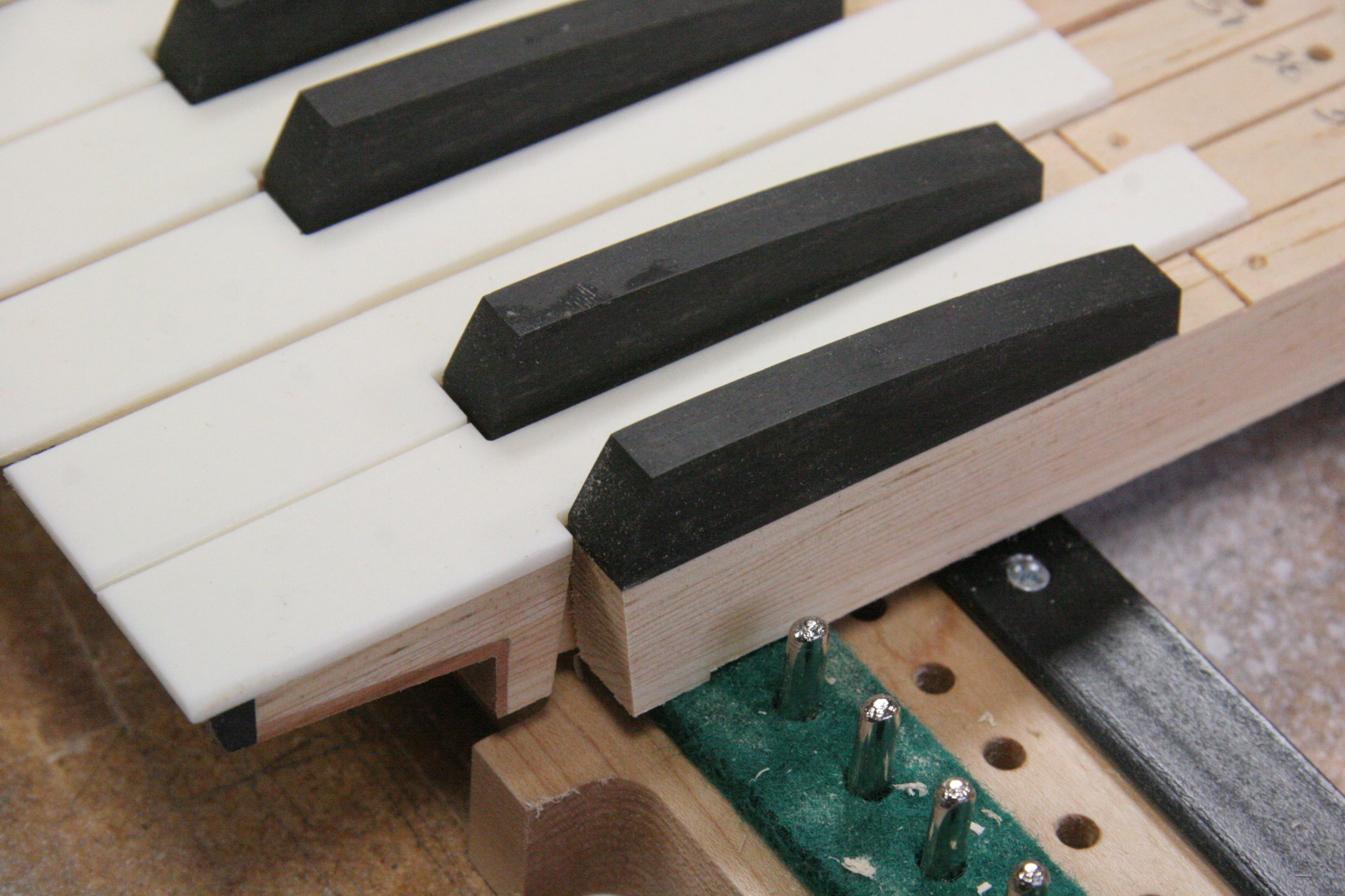 Construction detail showing cherry and ebony covers on key under-cut and sharps of ebony.