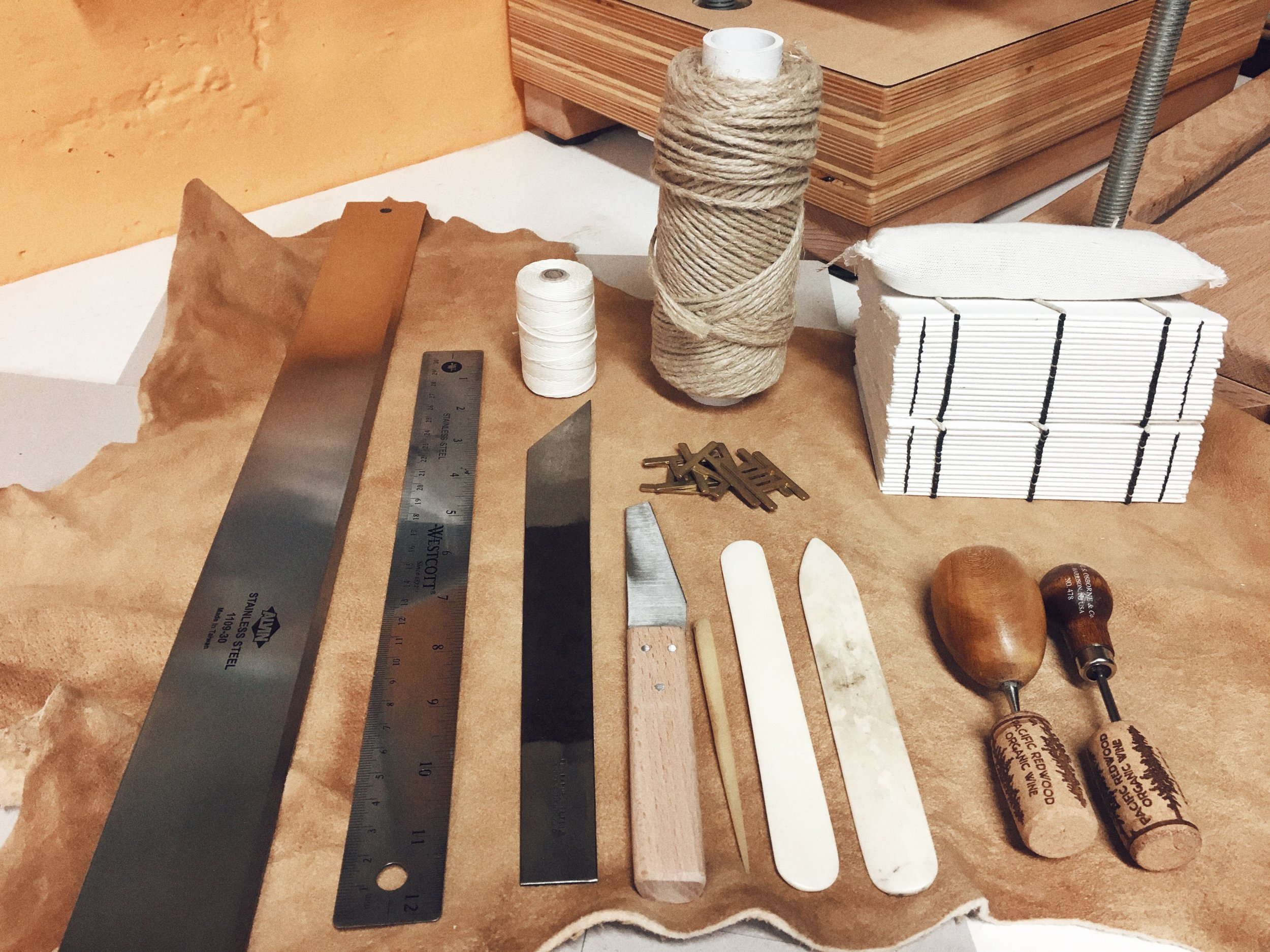 A selection of bookbinding tools. Clockwise from the top right : Blank text blocks, twine and linen thread, tear bar, ruler, English paring knife, leather knife, several bone folds and awls, and sewing keys in the middle. You can see hand-tanned leather as a backdrop and a bit of my press and sewing frame in the background.