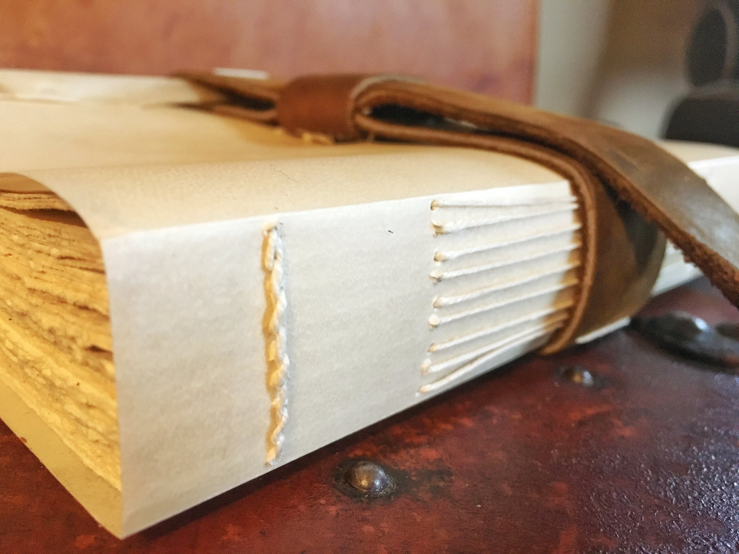 Simple long-stitch sewing on a closed spine of vellum.