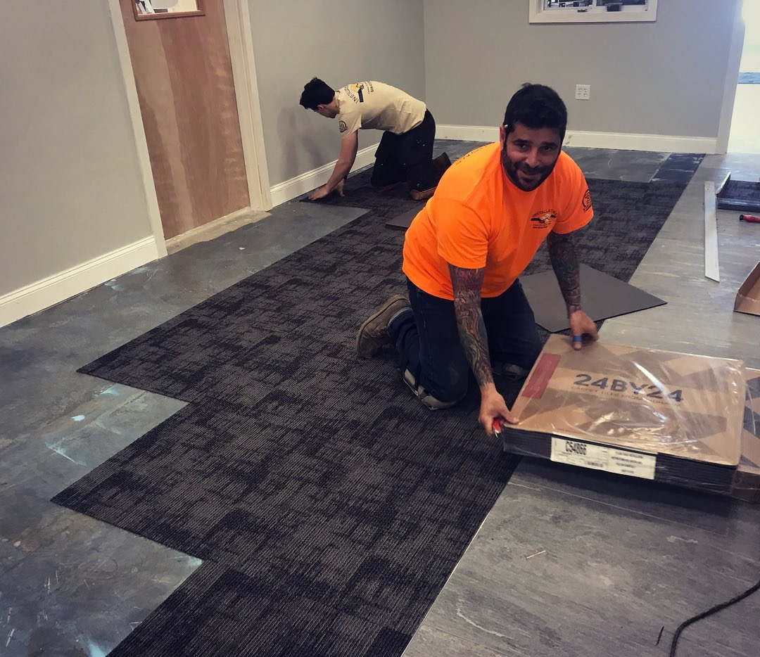 Happily installing carpet tile to pave the way for more cubicle space…
