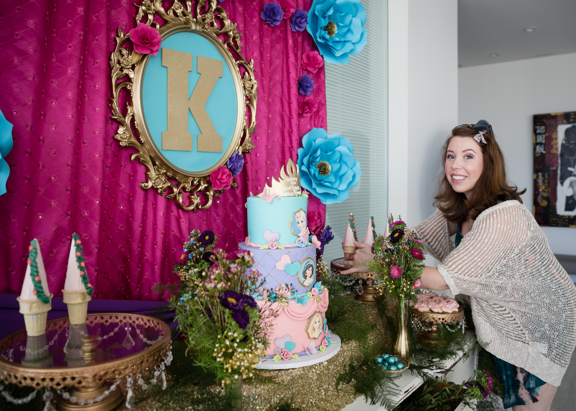 This is me making my finishing touches to the dessert table at an upscale princess party. The color palette was aqua, magenta, and violet with touches of gold. I was so in love with the florals our team designed for this event, and of course just look at that cake; t'was just as delicious as it was impressive. Photo by  Jeff Drongowski .