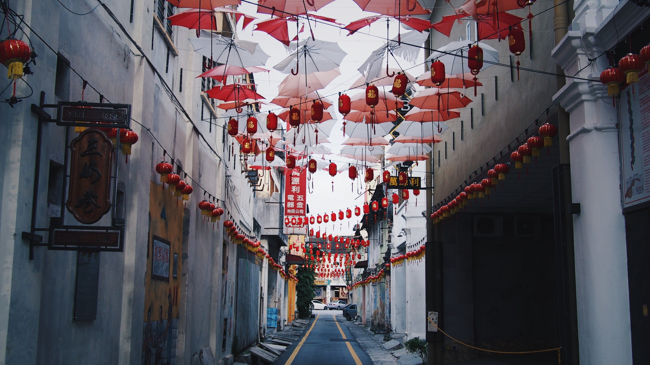 Red and white umbrellas hanging above a street in Ipoh, Malaysia