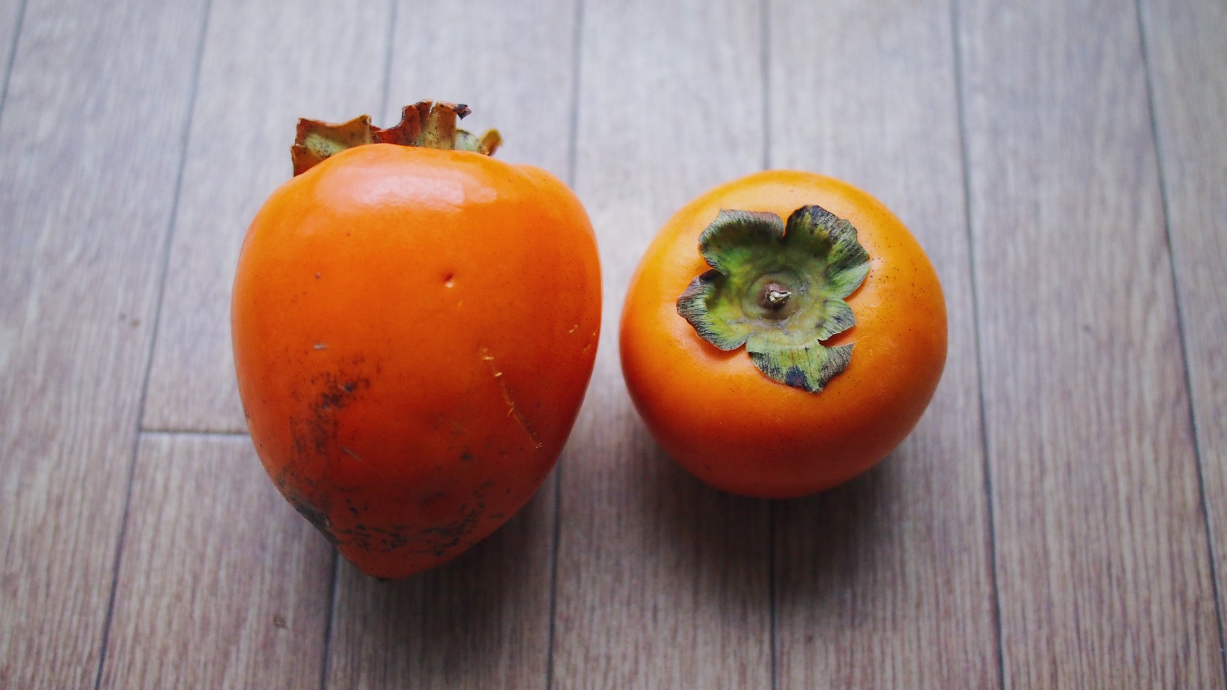 An unripe hachiya persimmon (left) and a fuyu persimmon (right)