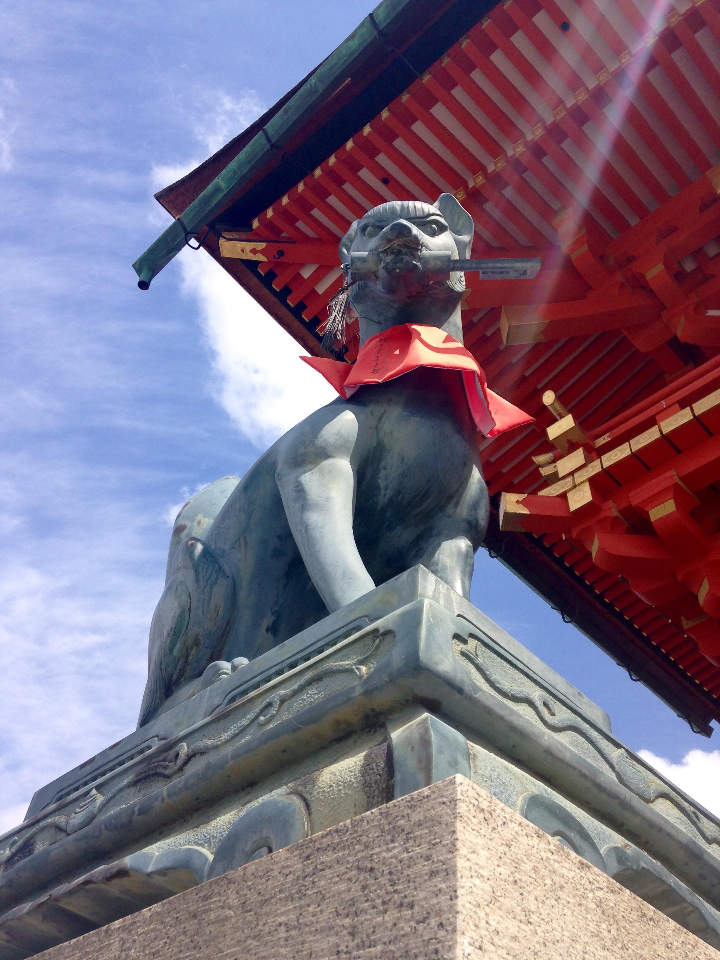 A menacing  kitsune  at the entrance to Fushimi Inari shrine .